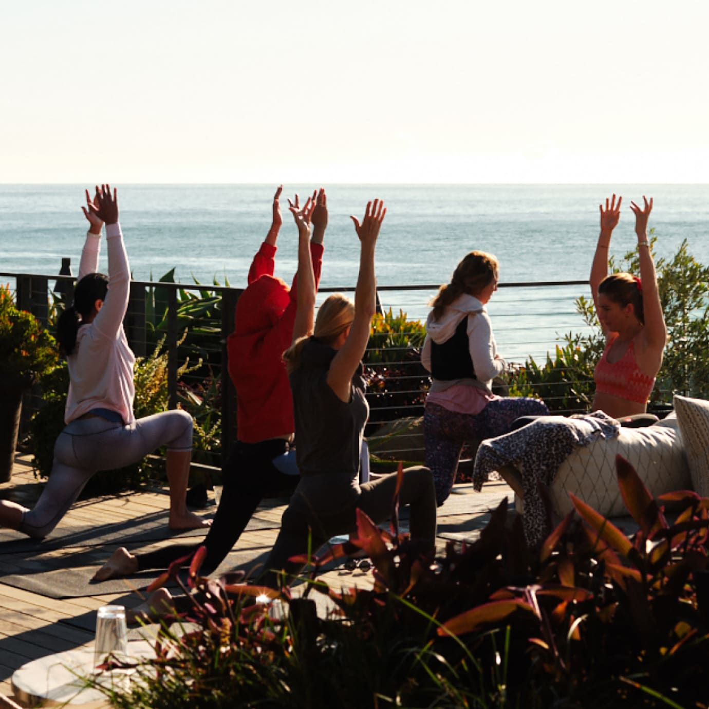 A group of people in a yoga class on an outdoor terrace overlooking the sea.