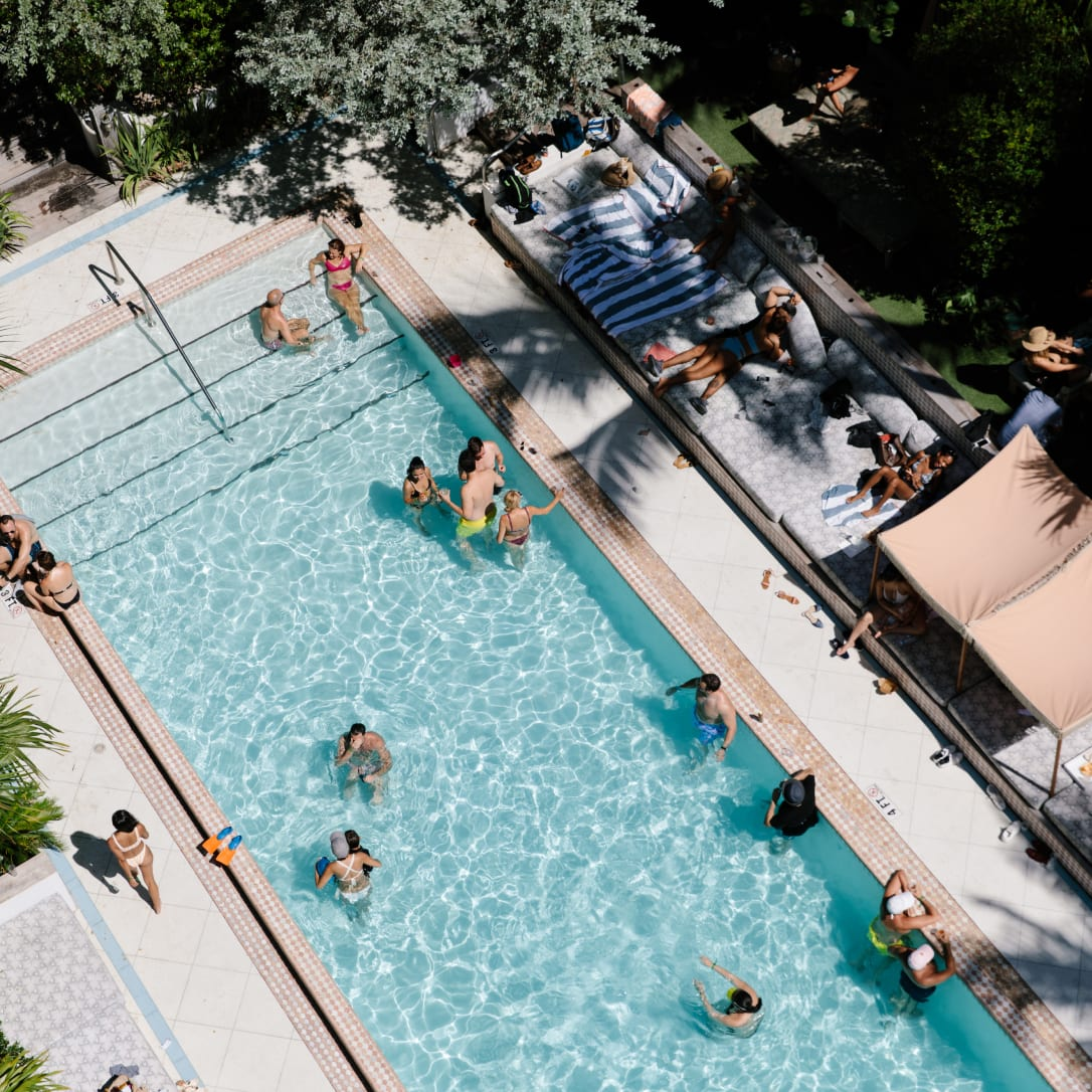 A swimming pool with various people in it.
