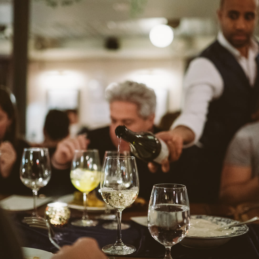 A waiter pours wine into a glass while people eat.
