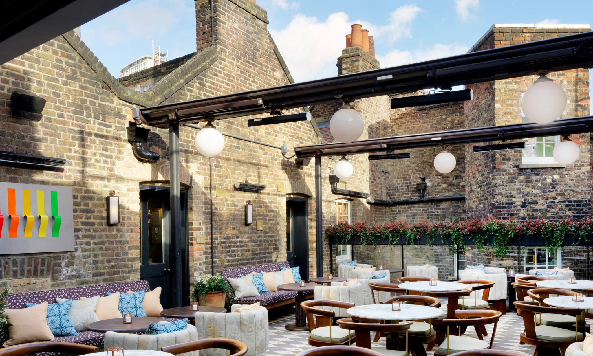 A roof terrace with many tables and chairs.