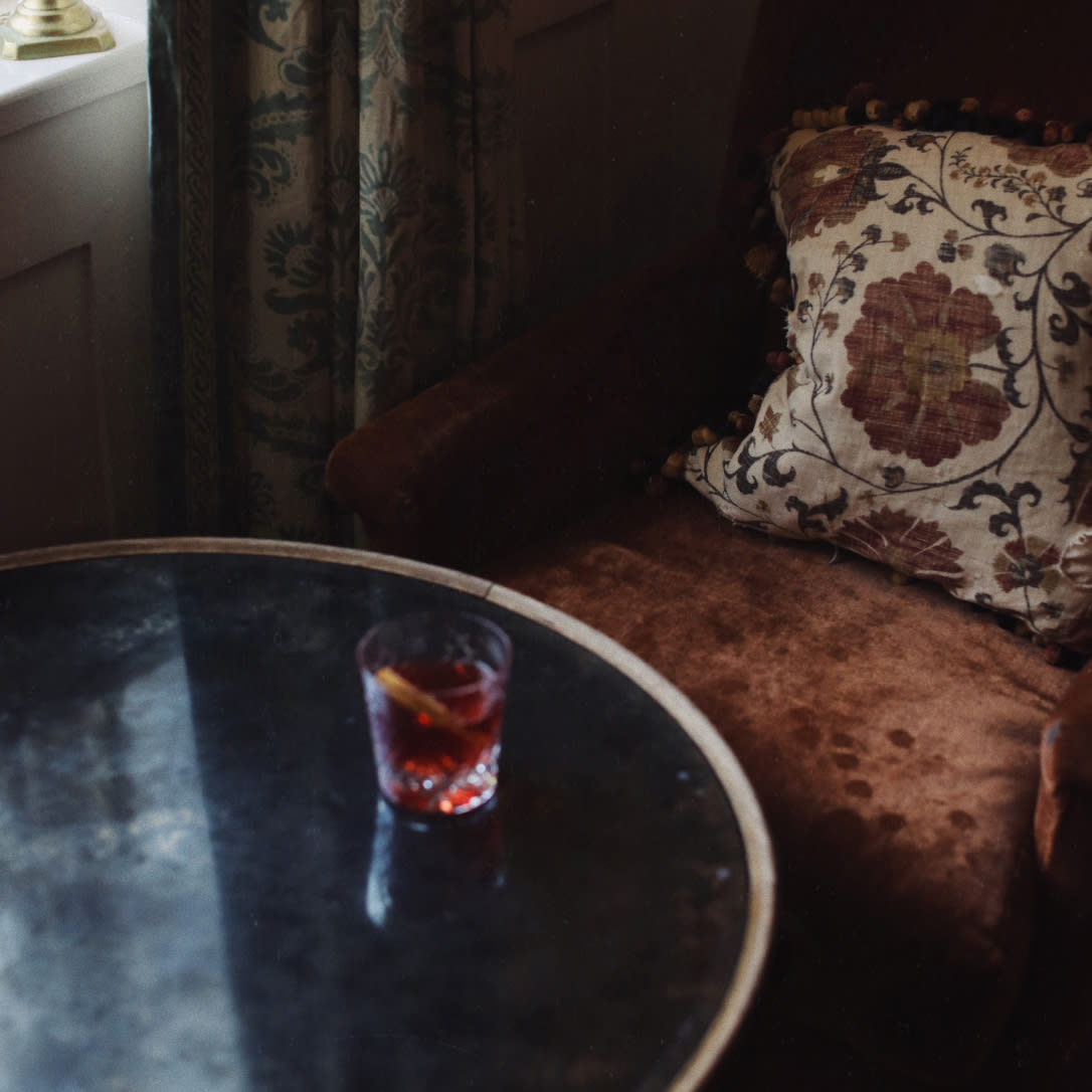 A cocktail on a table in a dark corner of a room.
