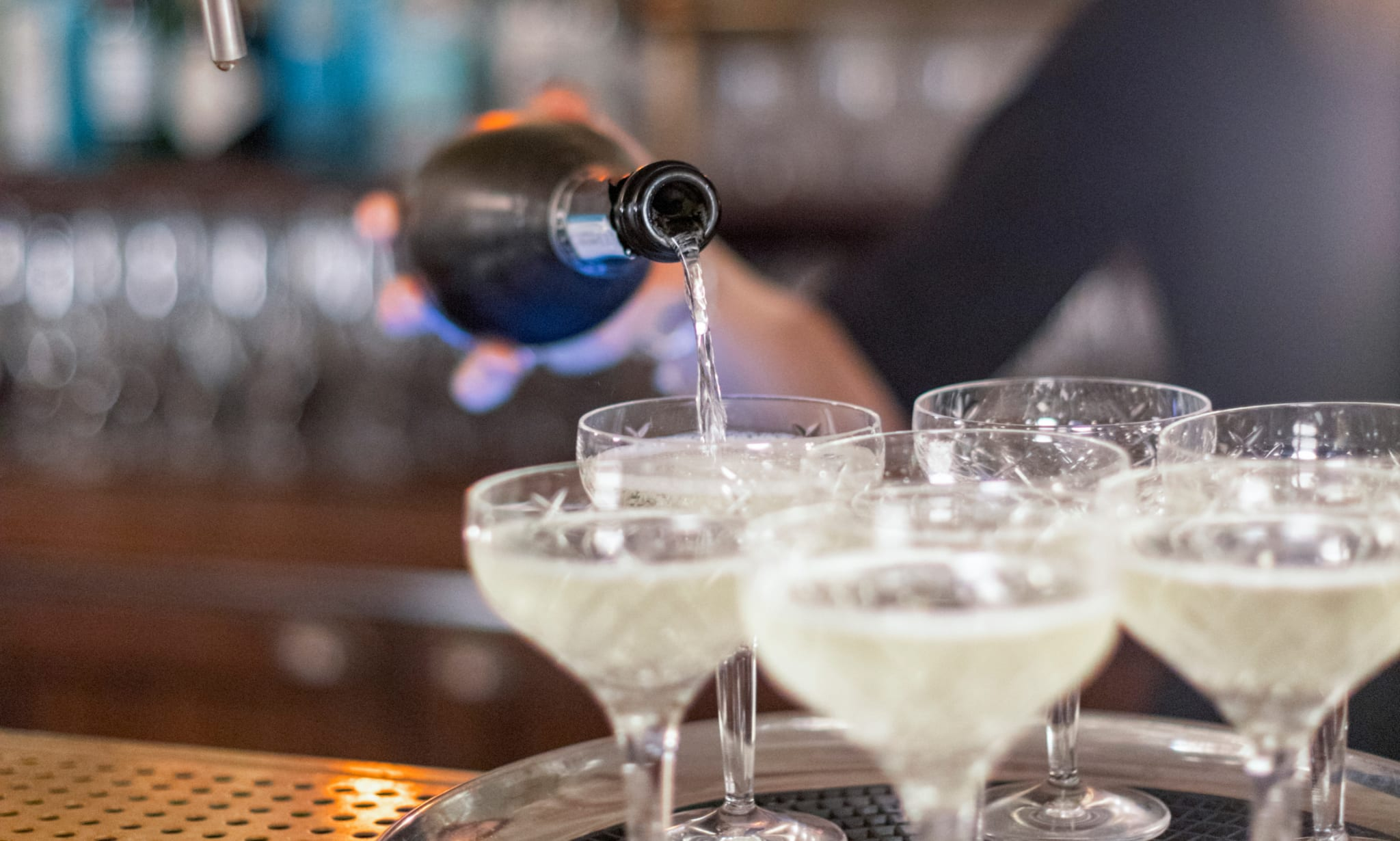 A bottle of champagne being poured into glasses on a bar.