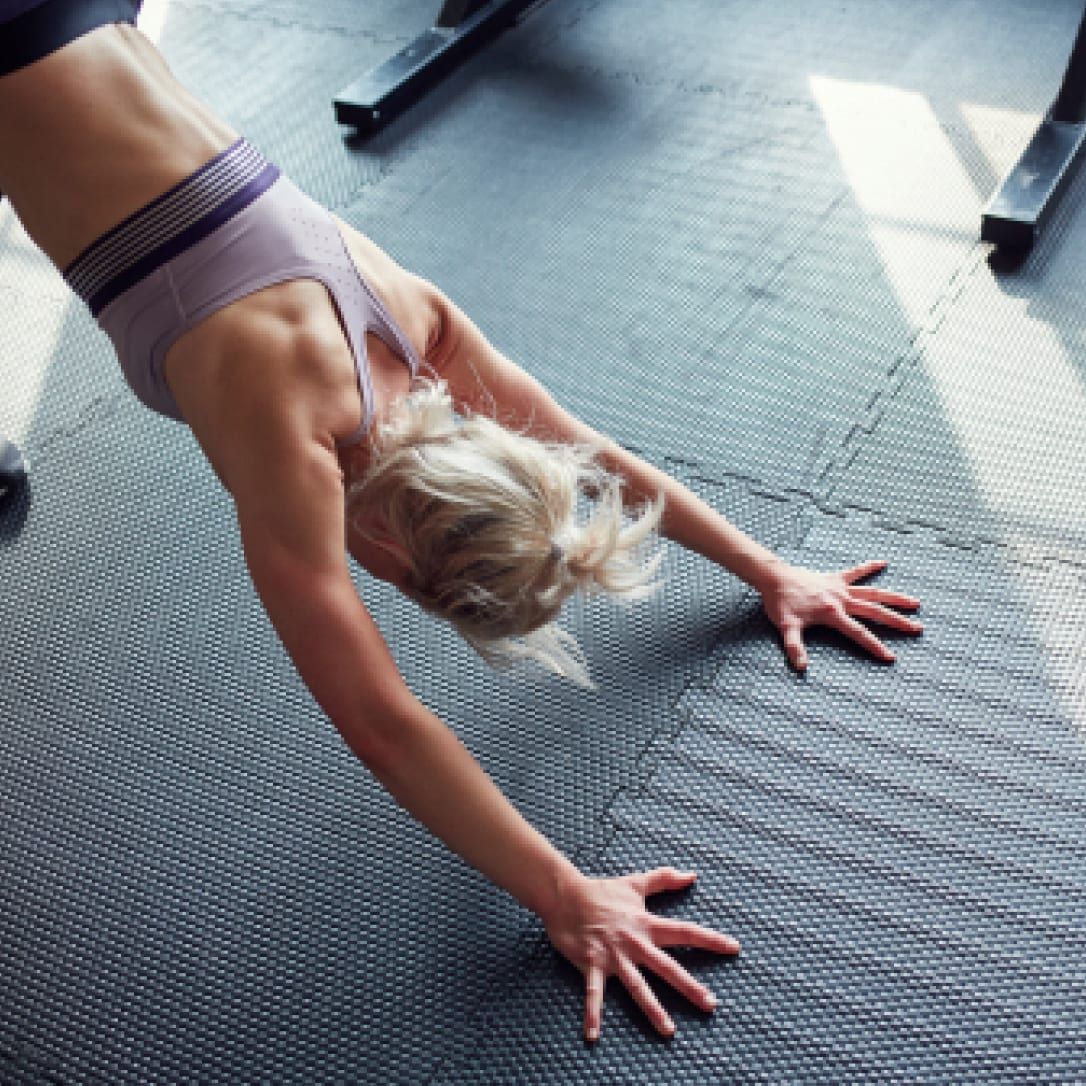 A woman stretches on the floor of a gym.