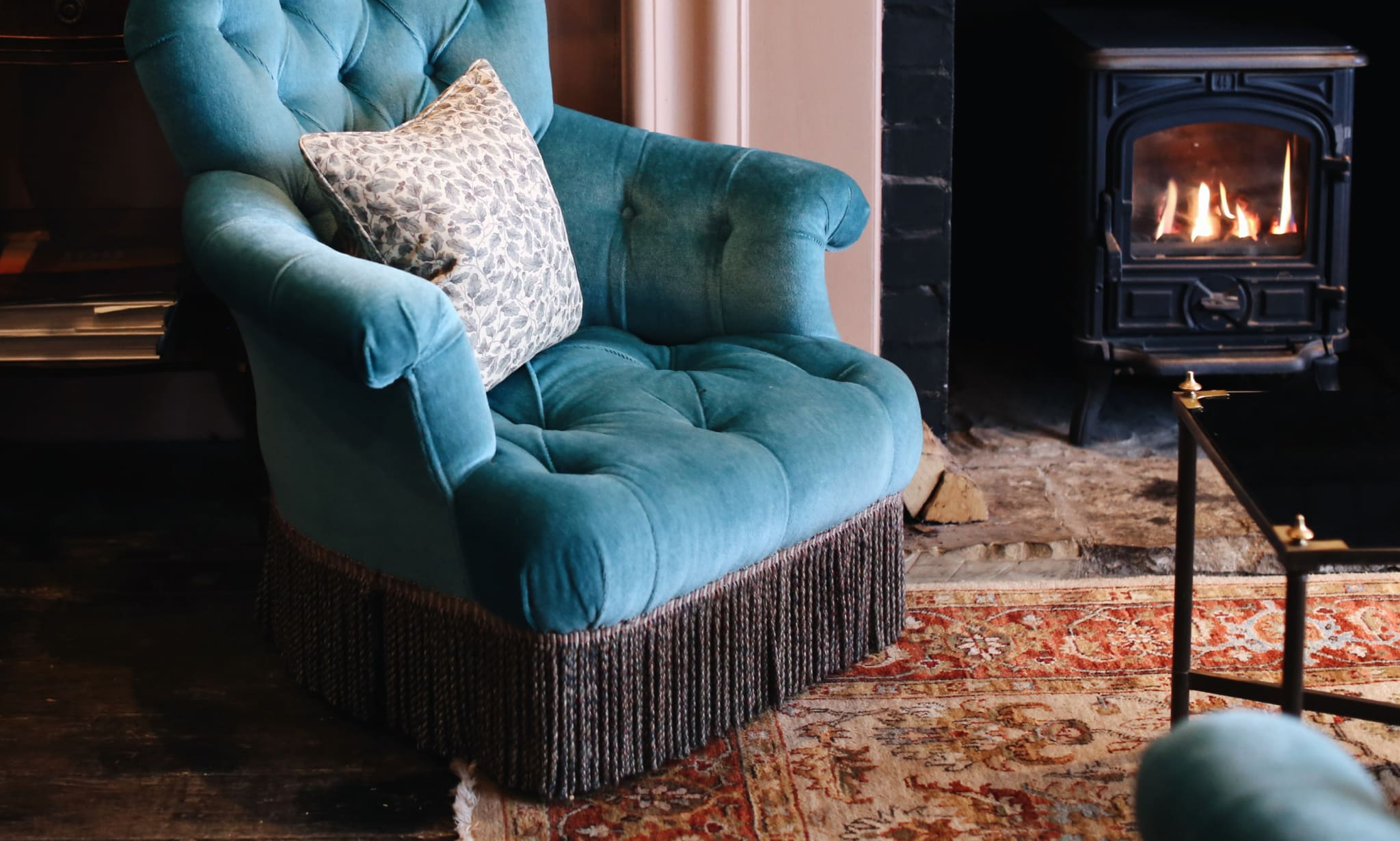 A blue armchair on a rug next to a lit wood burning stove