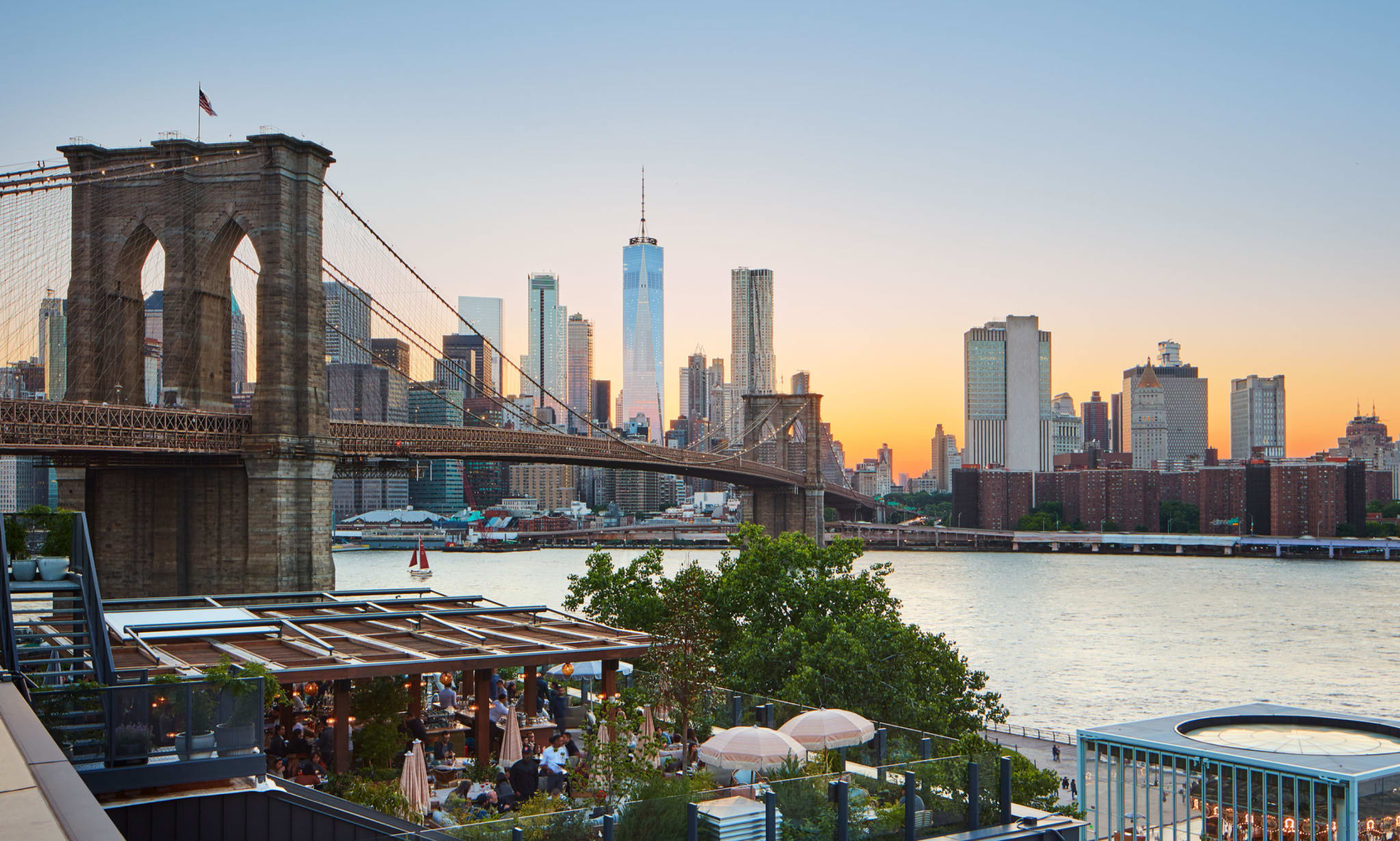 A restaurant's terrace overlooks the East River, Brooklyn Bridge and downtown Manhattan at sunset.