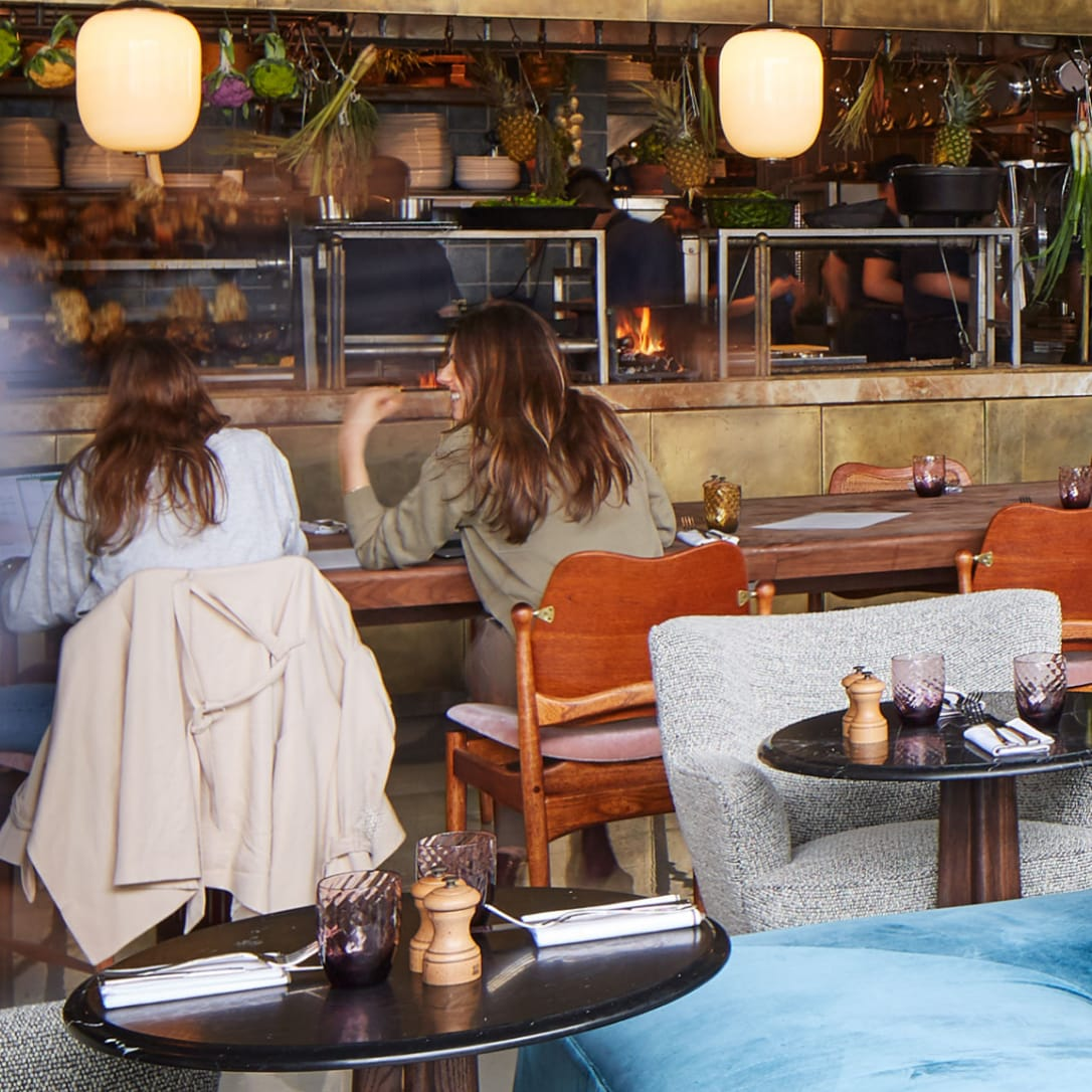 Two female diners chat while sitting at a table in a restaurant with an open plan kitchen.