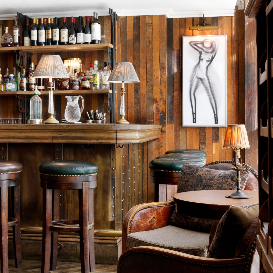 A bar with high stools and artwork on the walls.