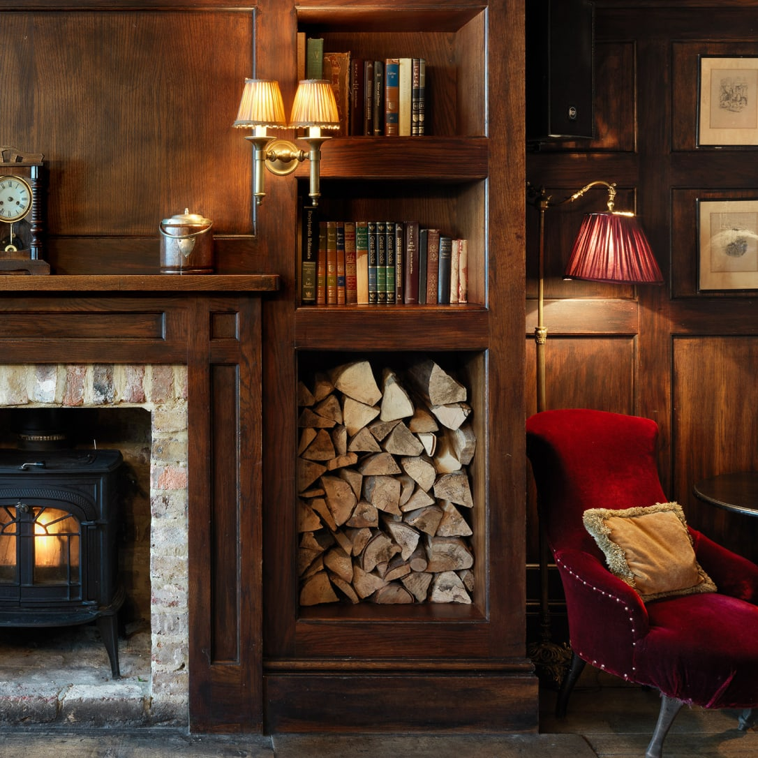 A wood panelled room with a fireplace an armchair and books on shelves.