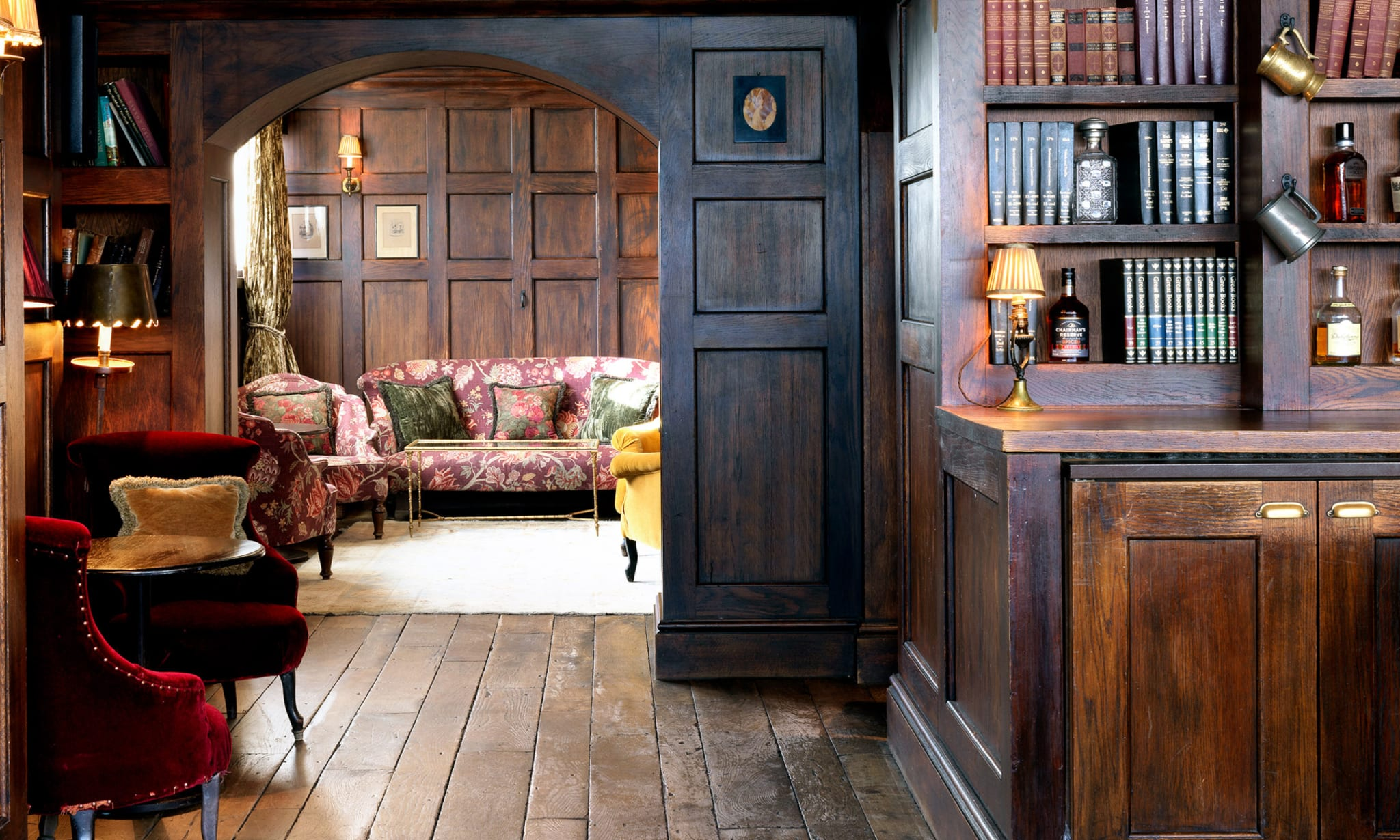 A wood panelled space with bookshelves and seating.