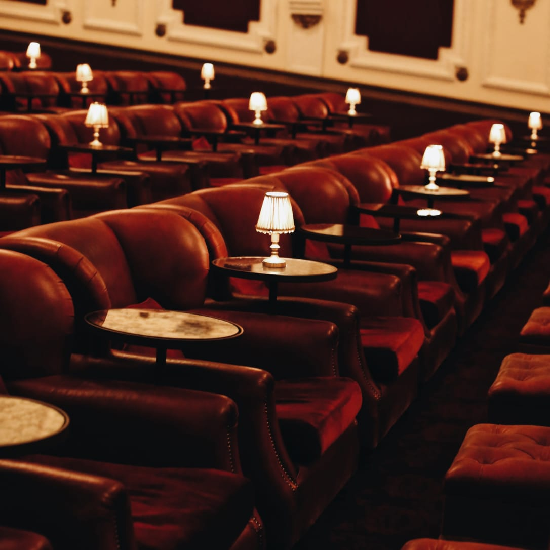 Rows of red cinema armchairs with side tables and lamps.