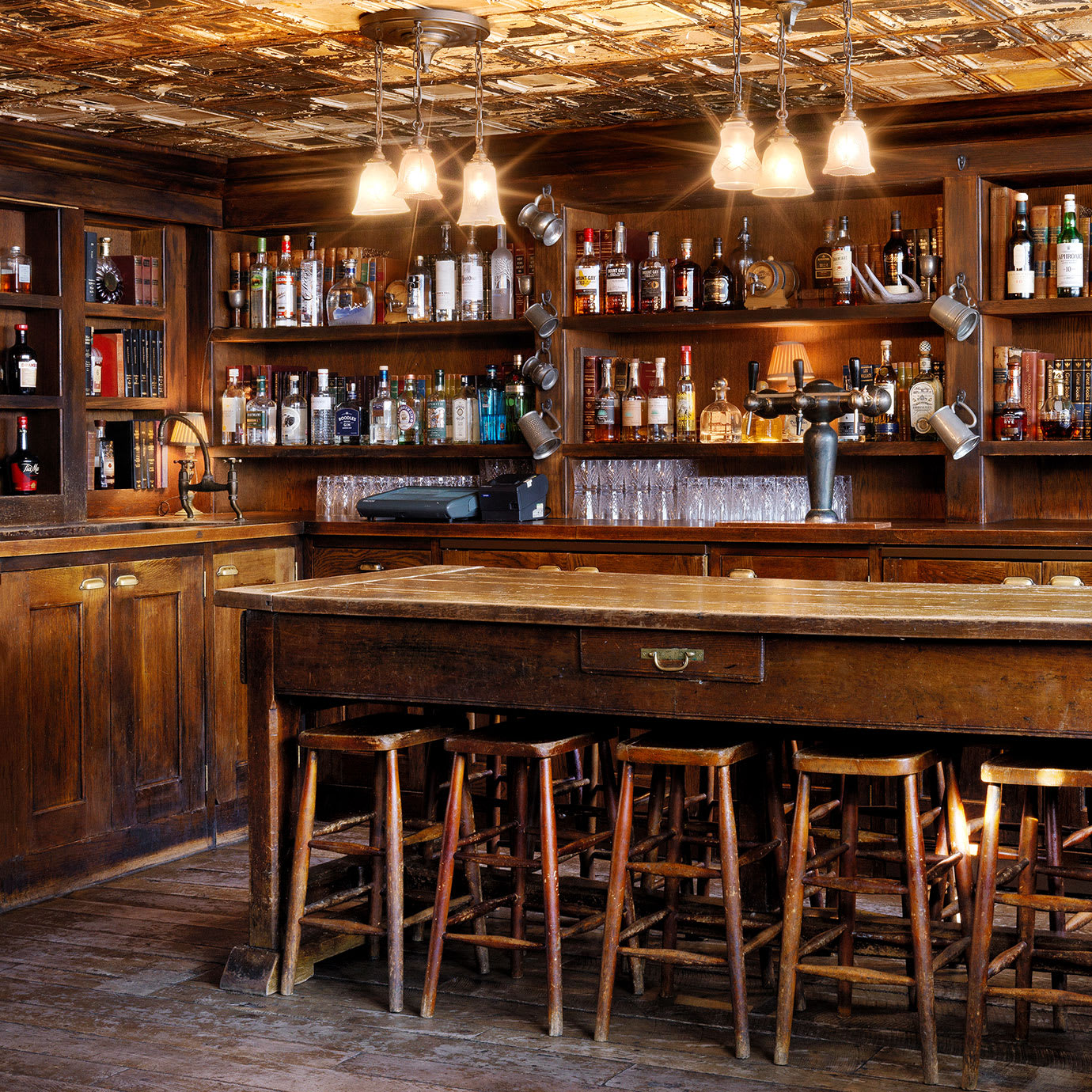 A wood panelled bar with a long table and stools.