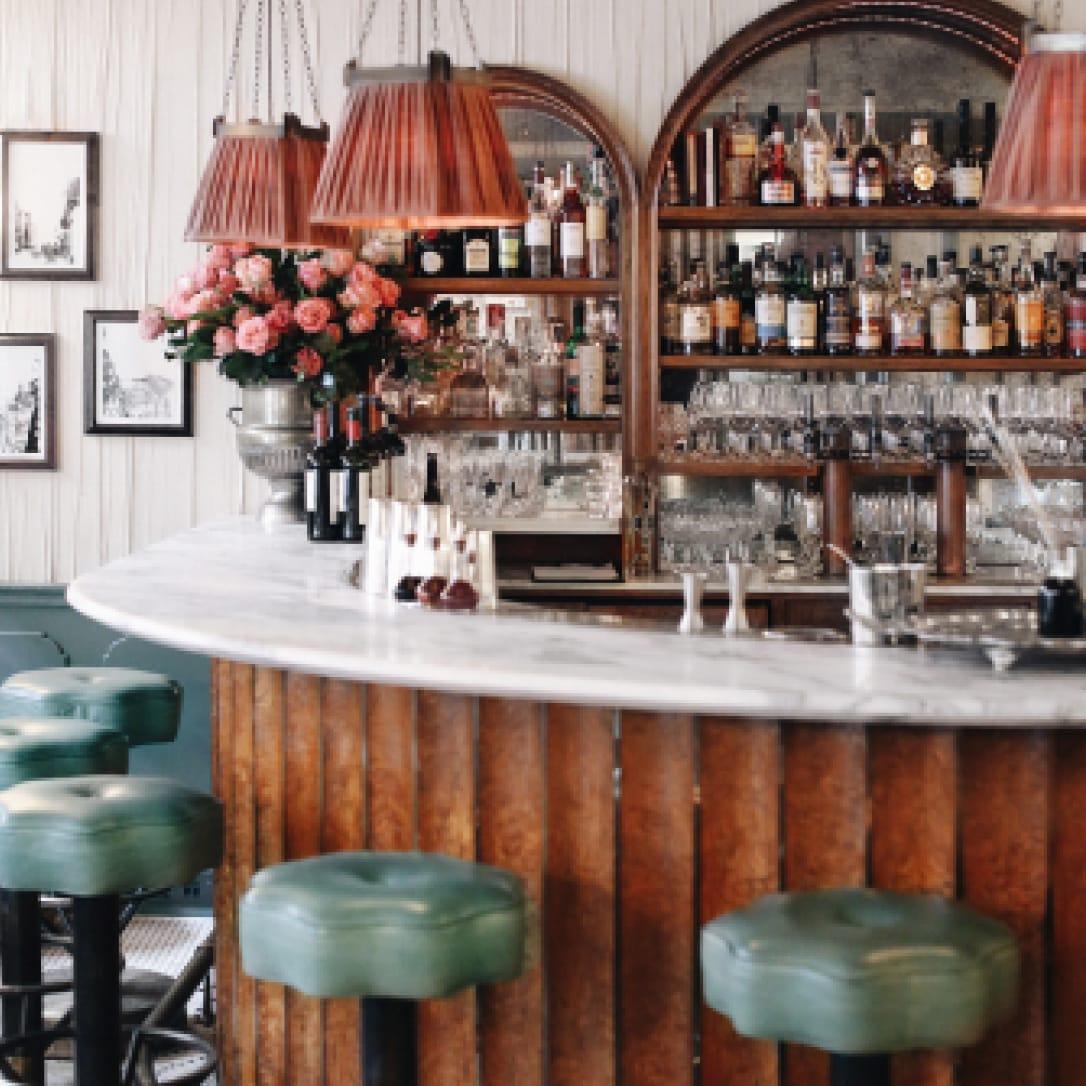 A semi circular marble bar with high chairs.