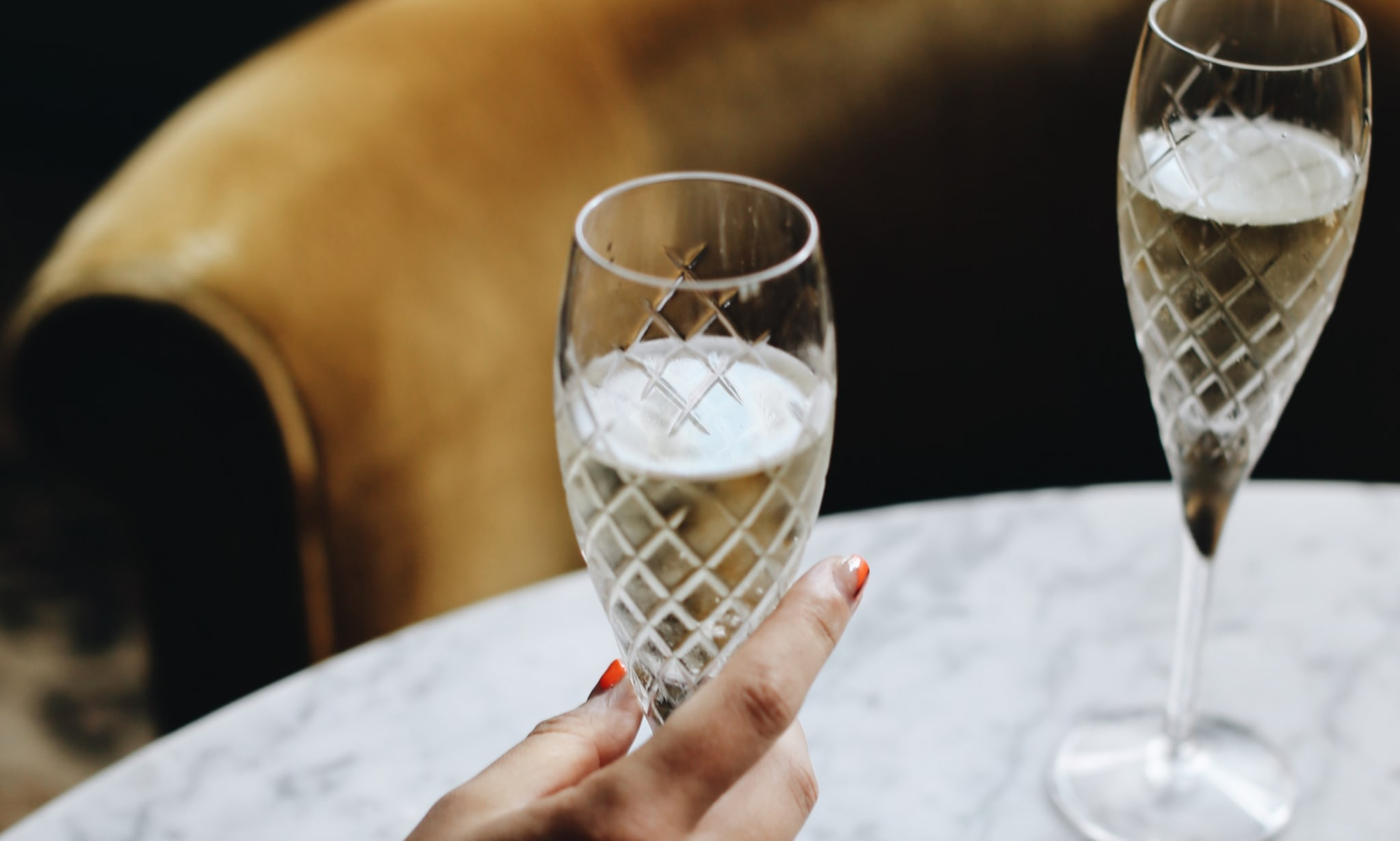 A woman holds a cut crystal champagne flute.