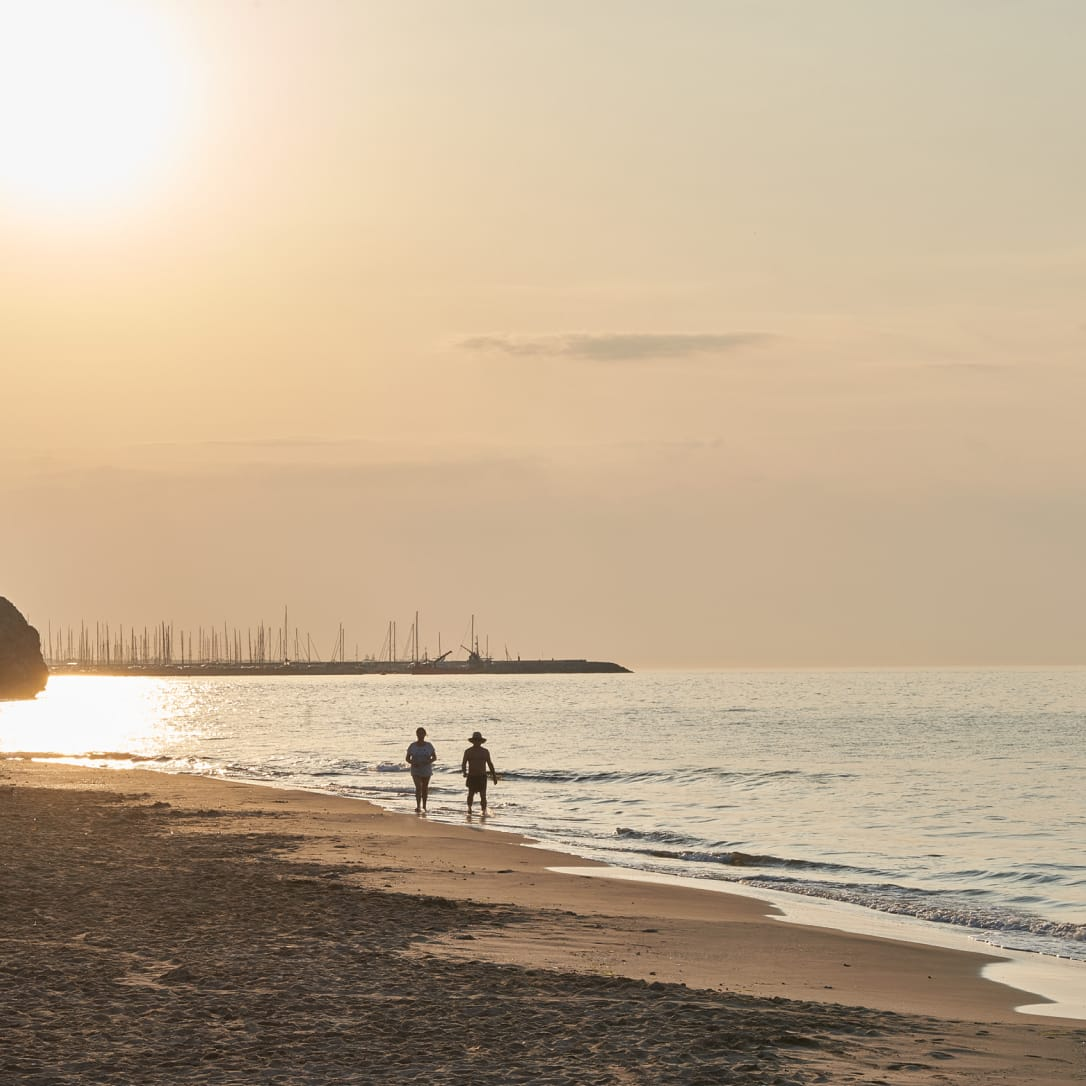 Two people walking down a beach at sunset.