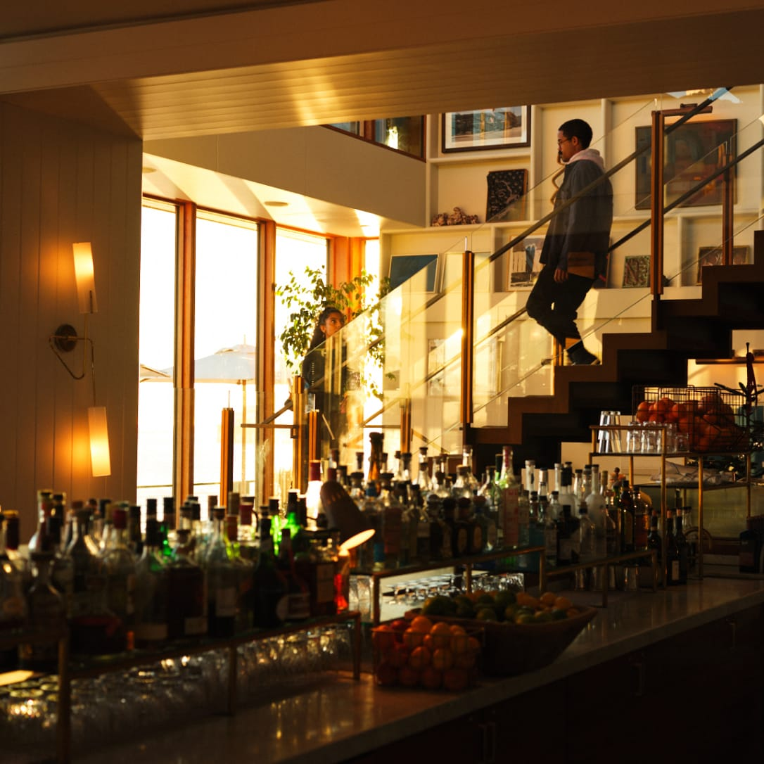 Two people walking down stairs into a bar area.