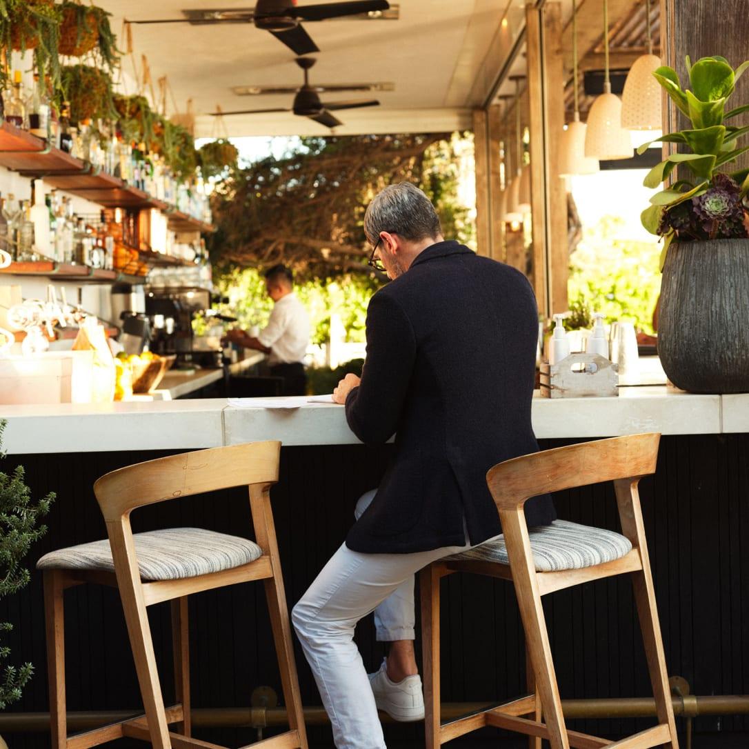 A man sits on a high stool at an outdoor bar.