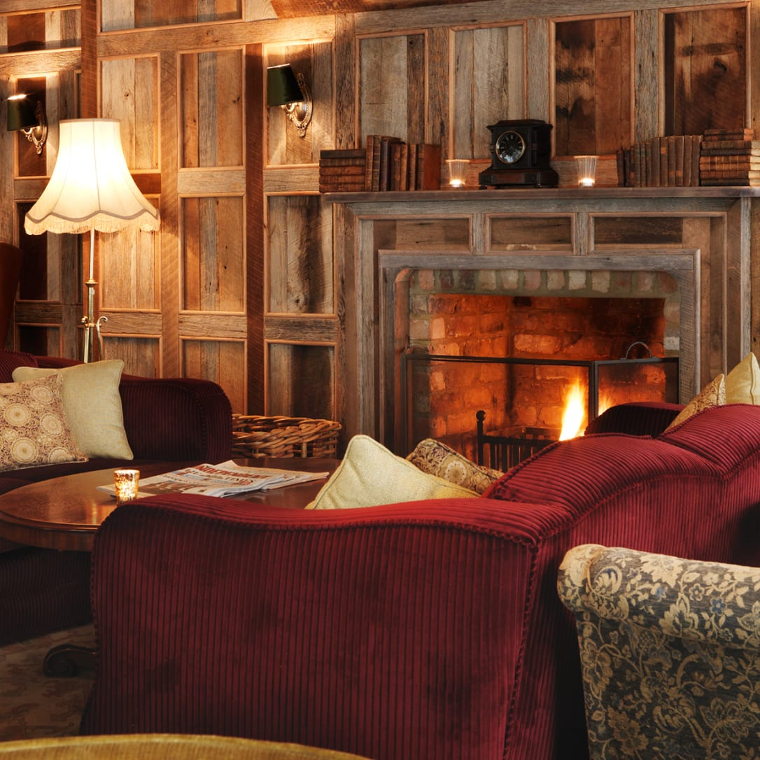 Sofas and chairs around a fireplace in a wood panelled room.