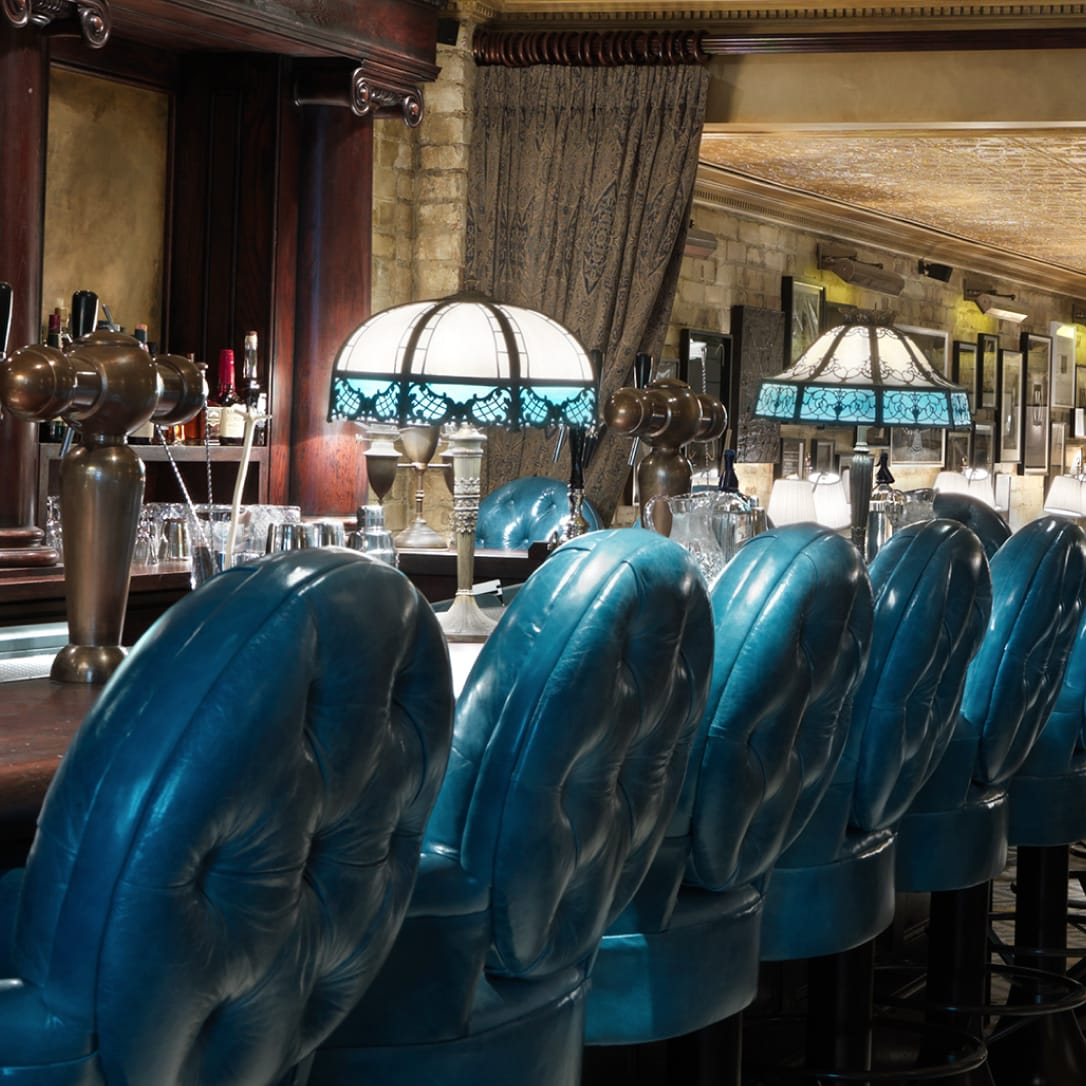 A bar with blue high chairs.