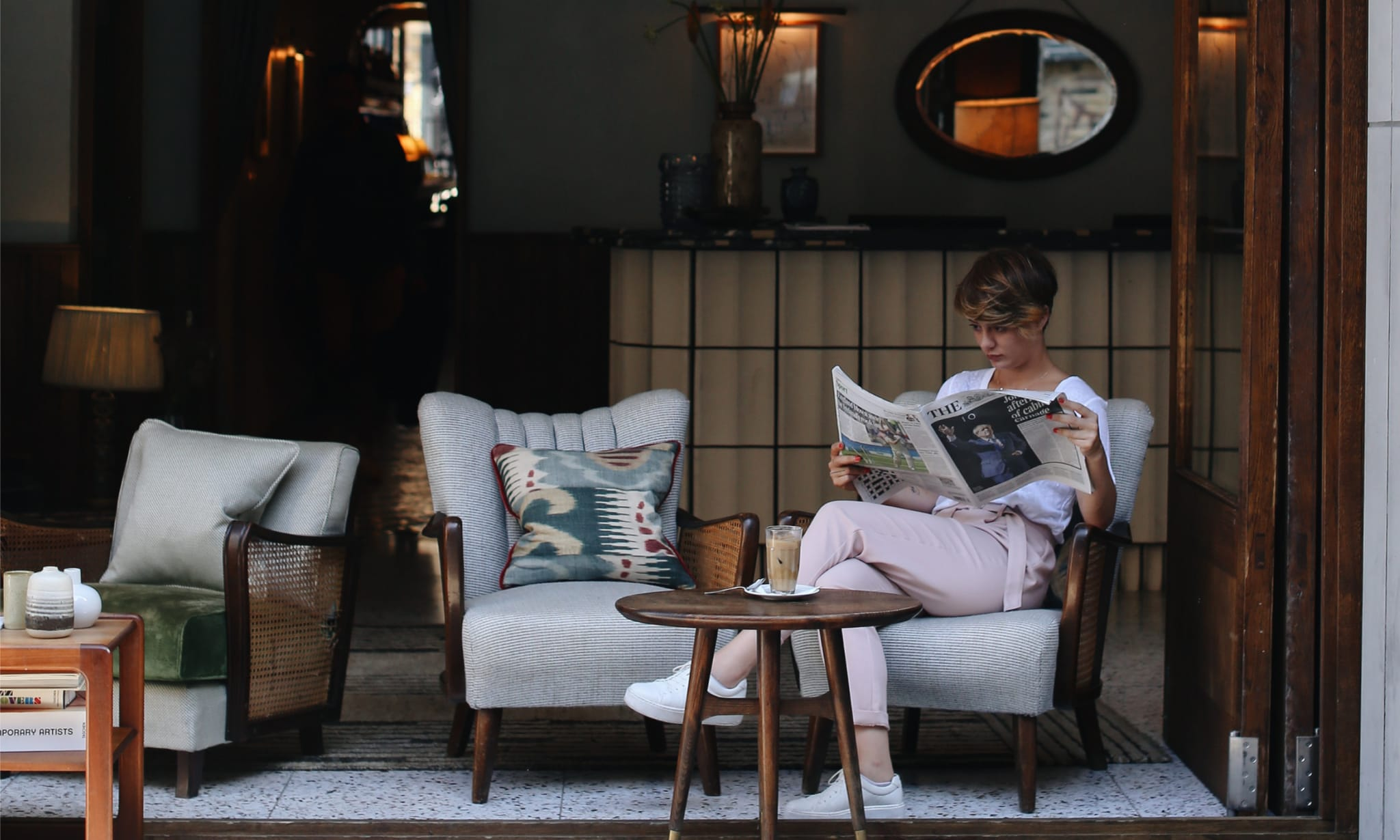 A woman reading a newspaper by open sliding doors in the lobby of a hotel.