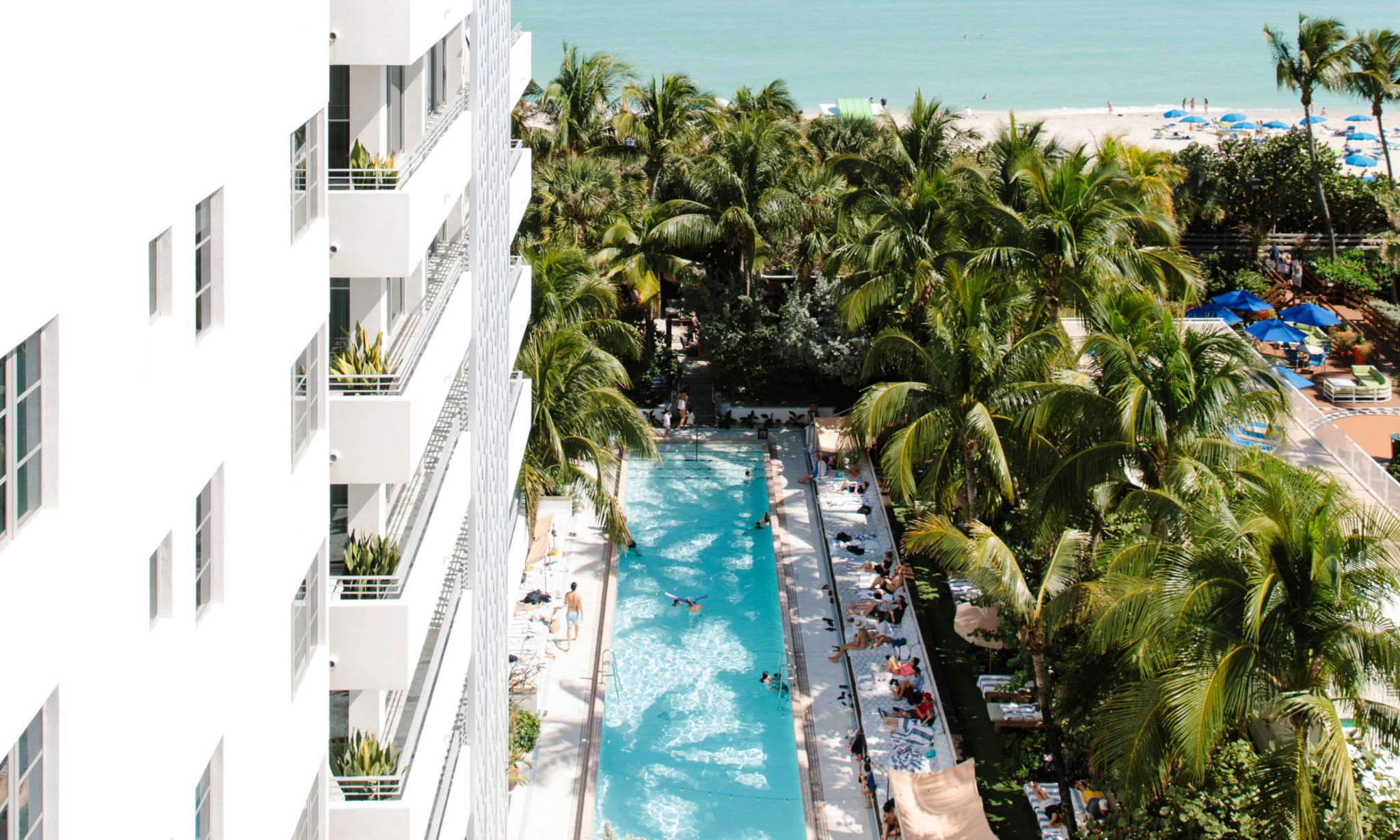 Looking down onto a pool and beach area from the top of a white building.