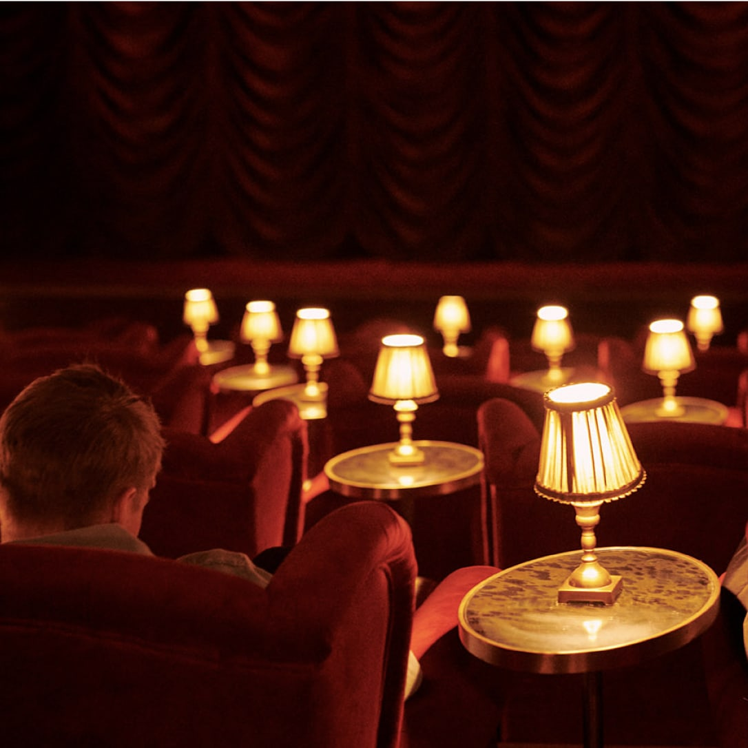 A red cinema auditorium decorated with side tables and lamps, with a man sitting in a chair.