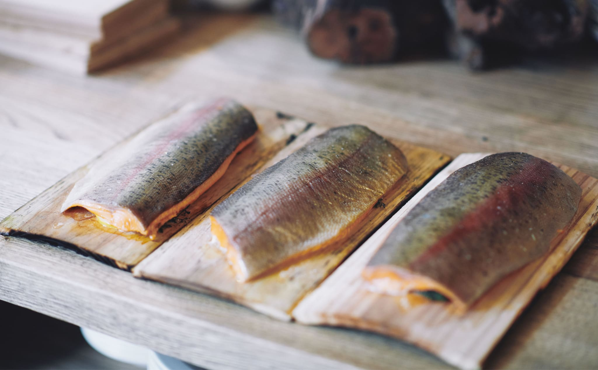 Three raw fish fillets on wooden trays.