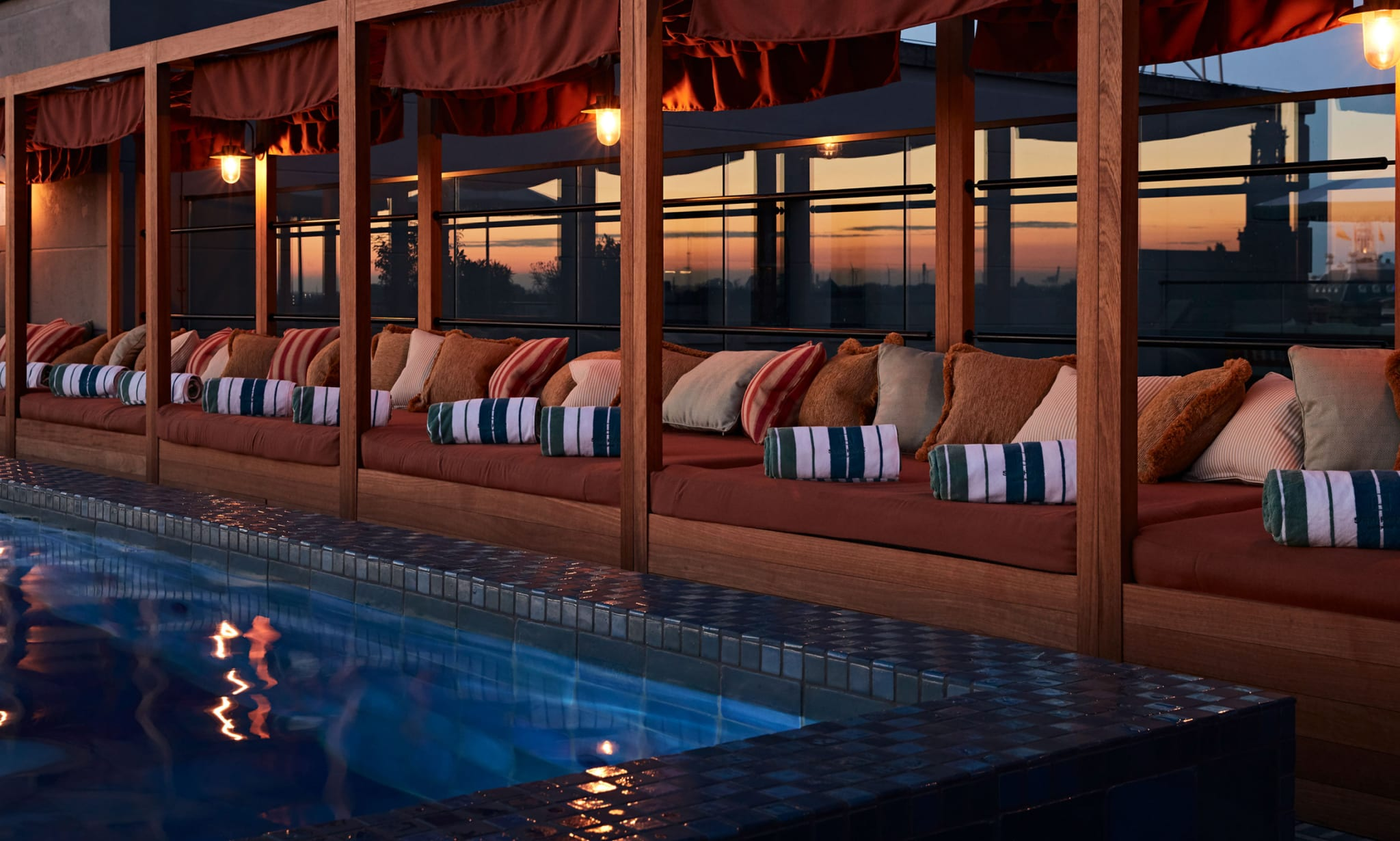 A rooftop pool with daybeds at sunset.