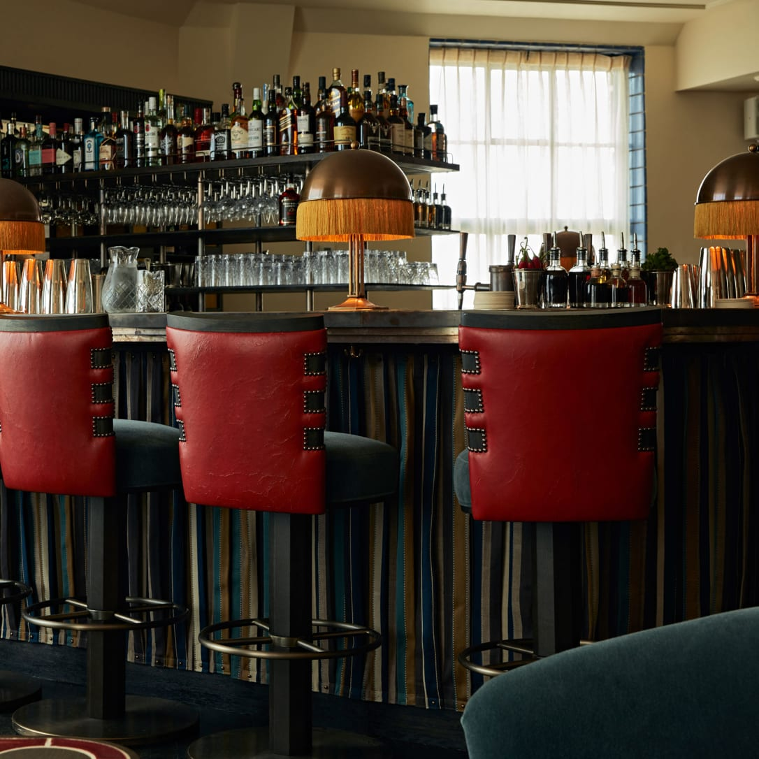 A bar with red high stools.