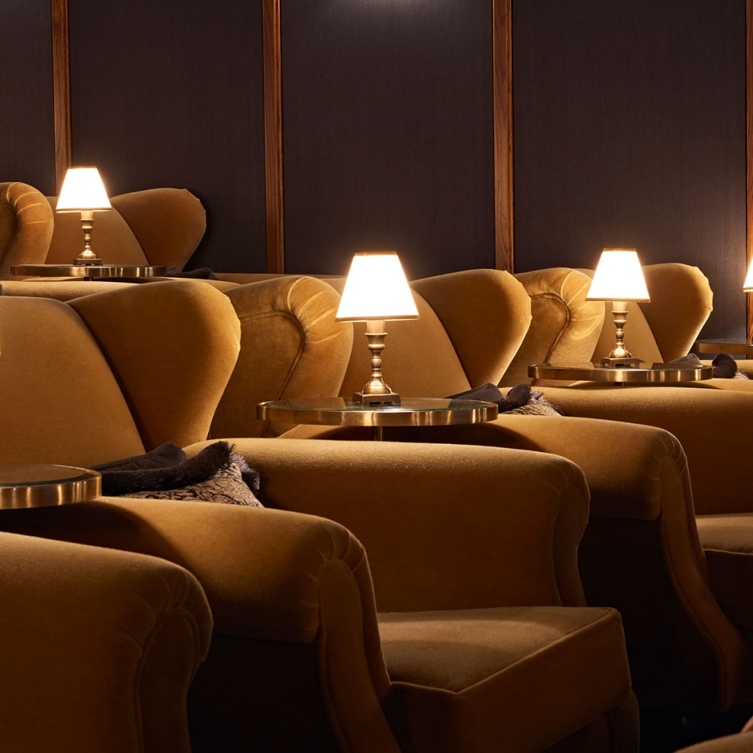 Cinema seating with side tables and lamps.