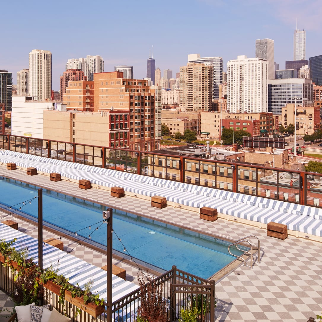 A rooftop with pool overlooking a city.