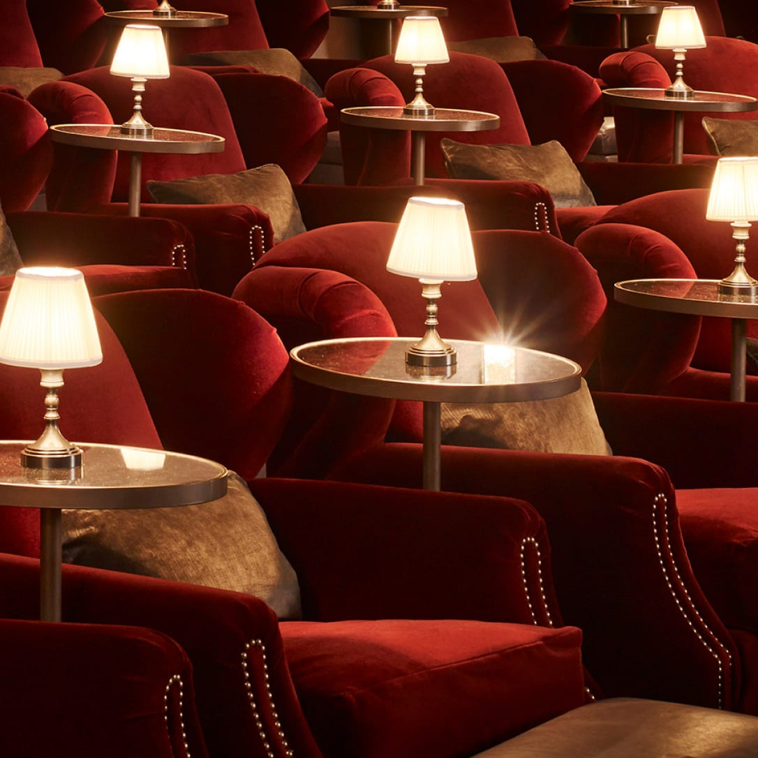 A close up of large red cinema chairs with side tables and lamps.