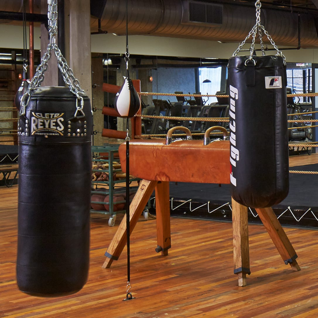 Two punch bags in a gym.