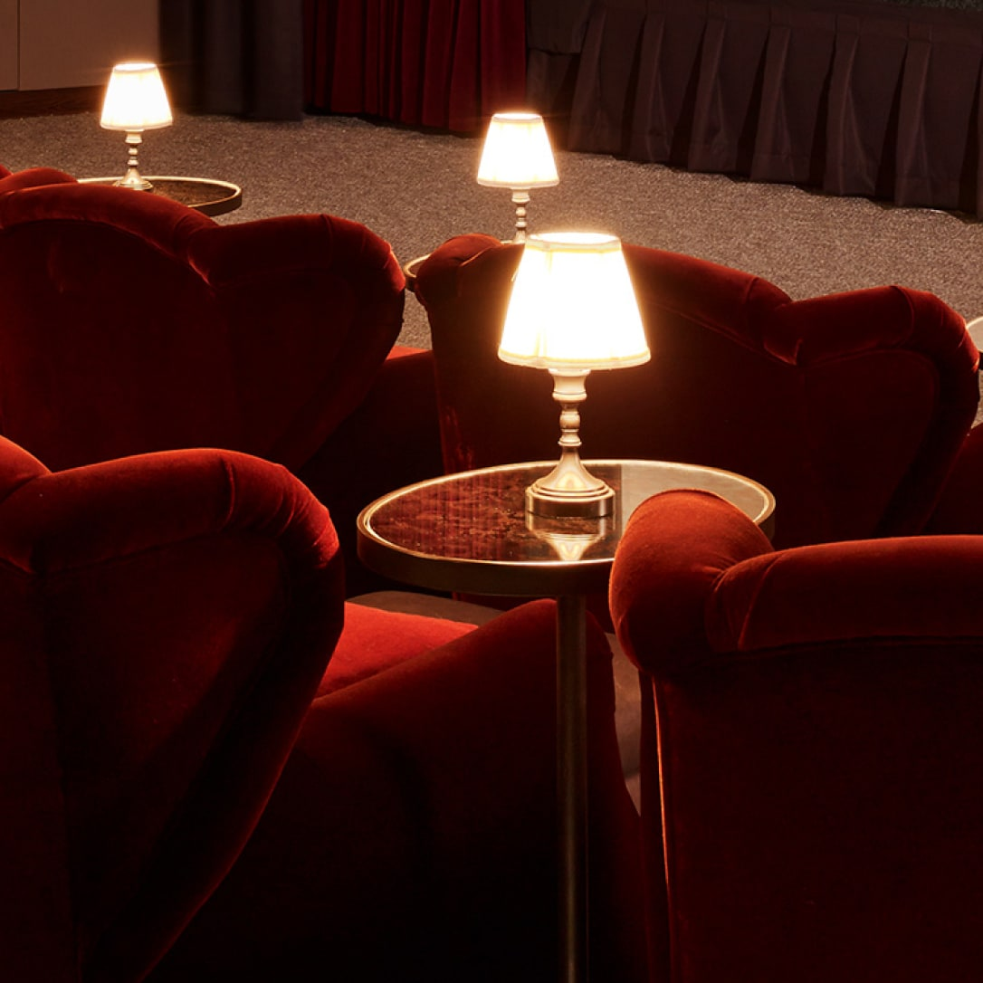 A row of red cinema seating with side tables and lamps.
