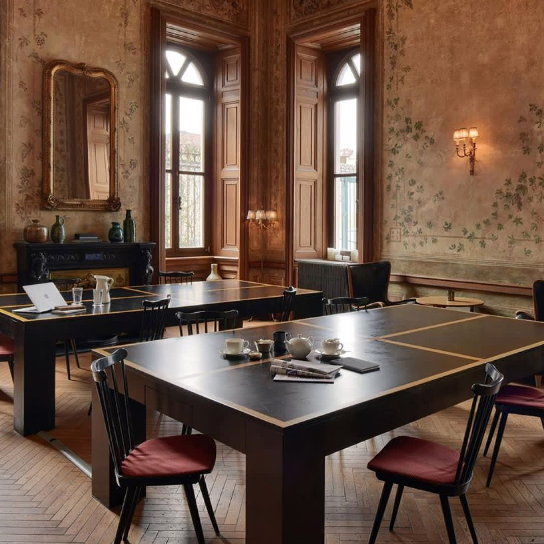 An ornate high ceilinged room with dark tables that are also ping pong tables.