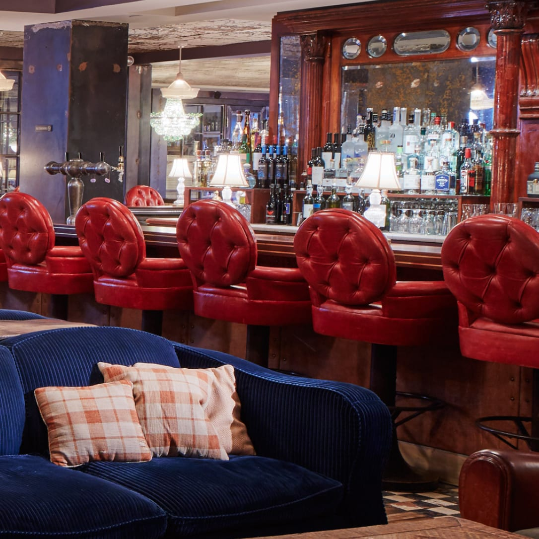 A wooden bar with red leather high chairs.