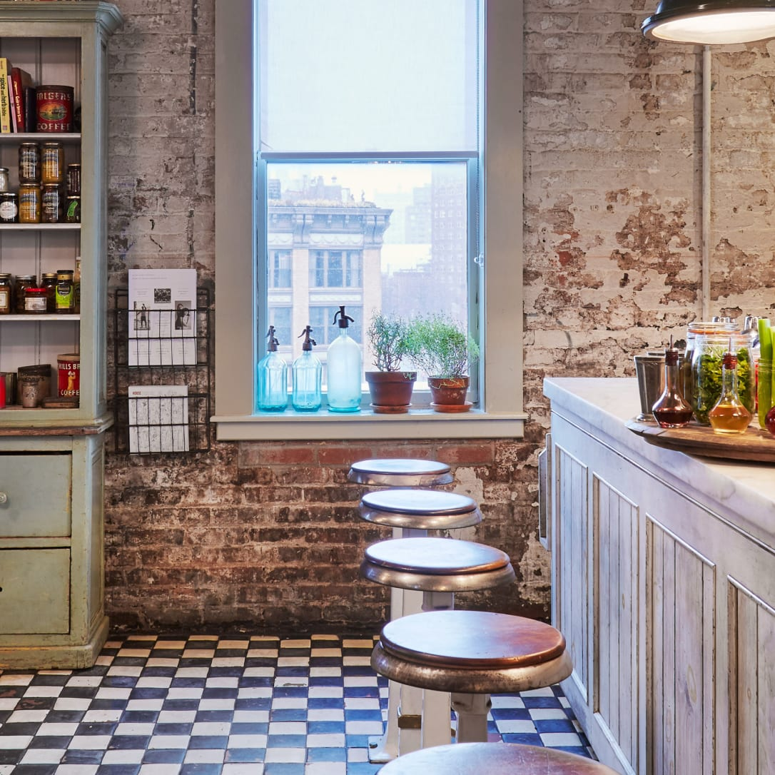 A pantry style interior with whitewashed walls and stools.