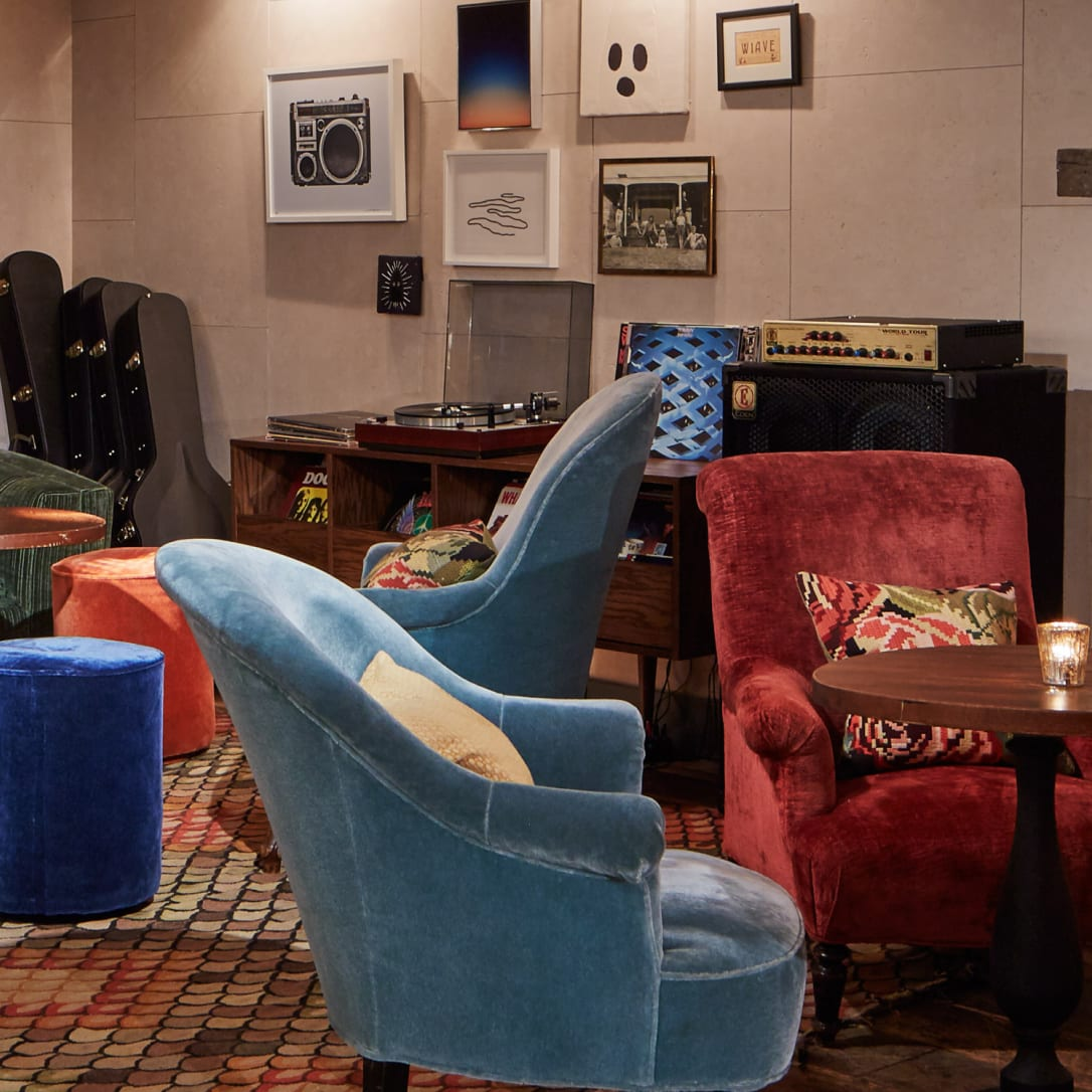 Various armchairs with a record player and vinyl in the background.