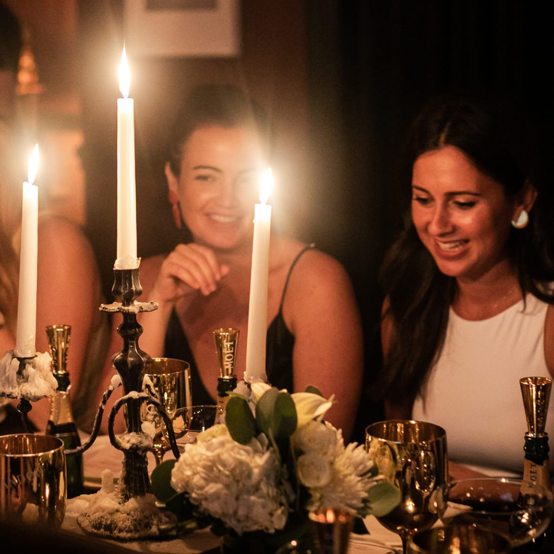 Women enjoying a formal dinner with candels.
