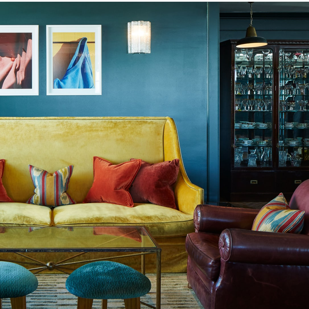 A yellow sofa in a blue room.