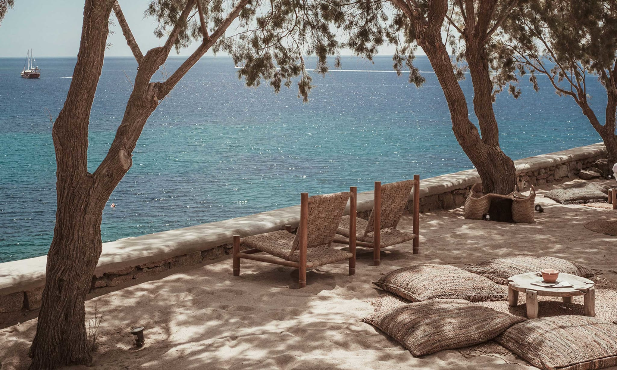 Two loungers overlooking the sea underneath some trees.