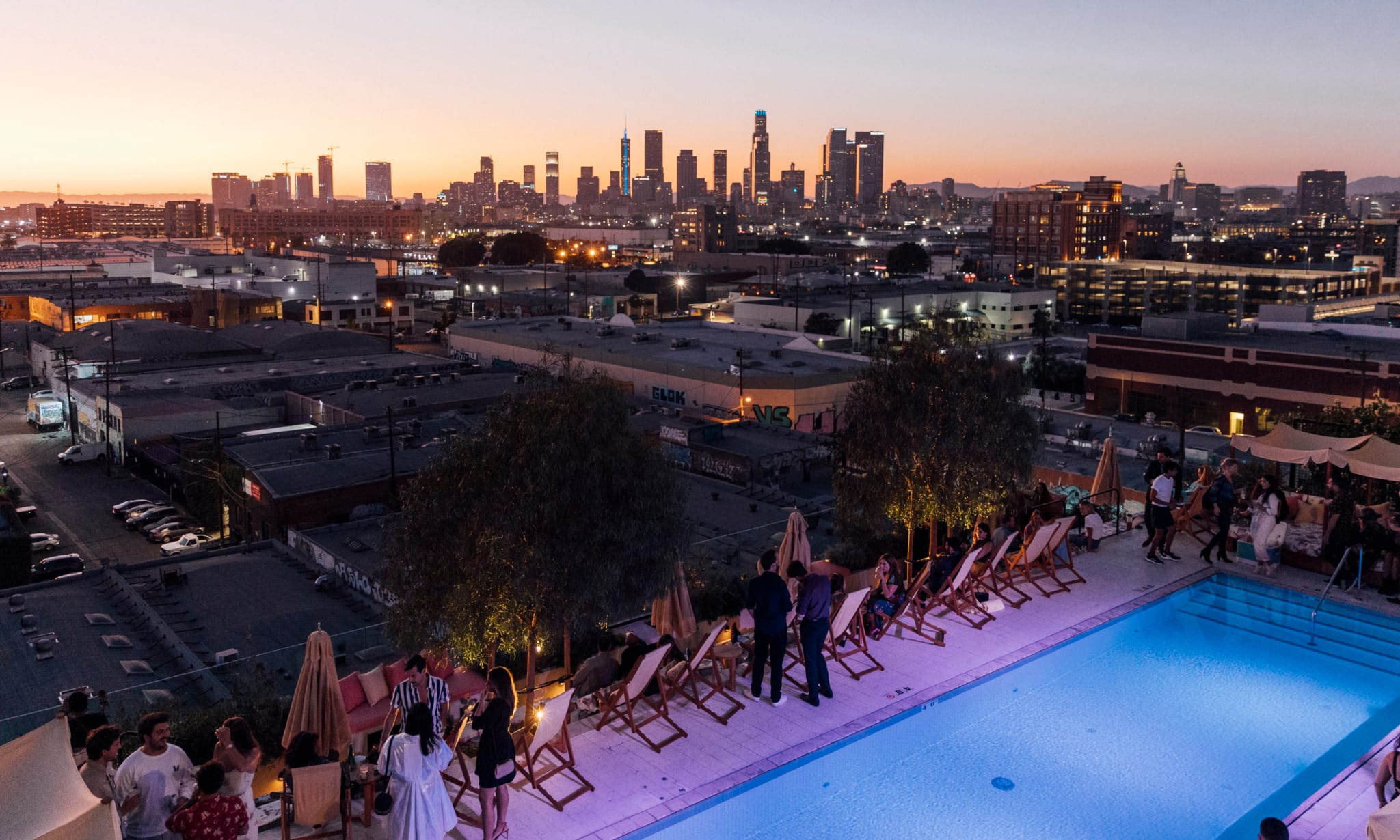 A rooftop pool surrounded by deckchairs and loungers