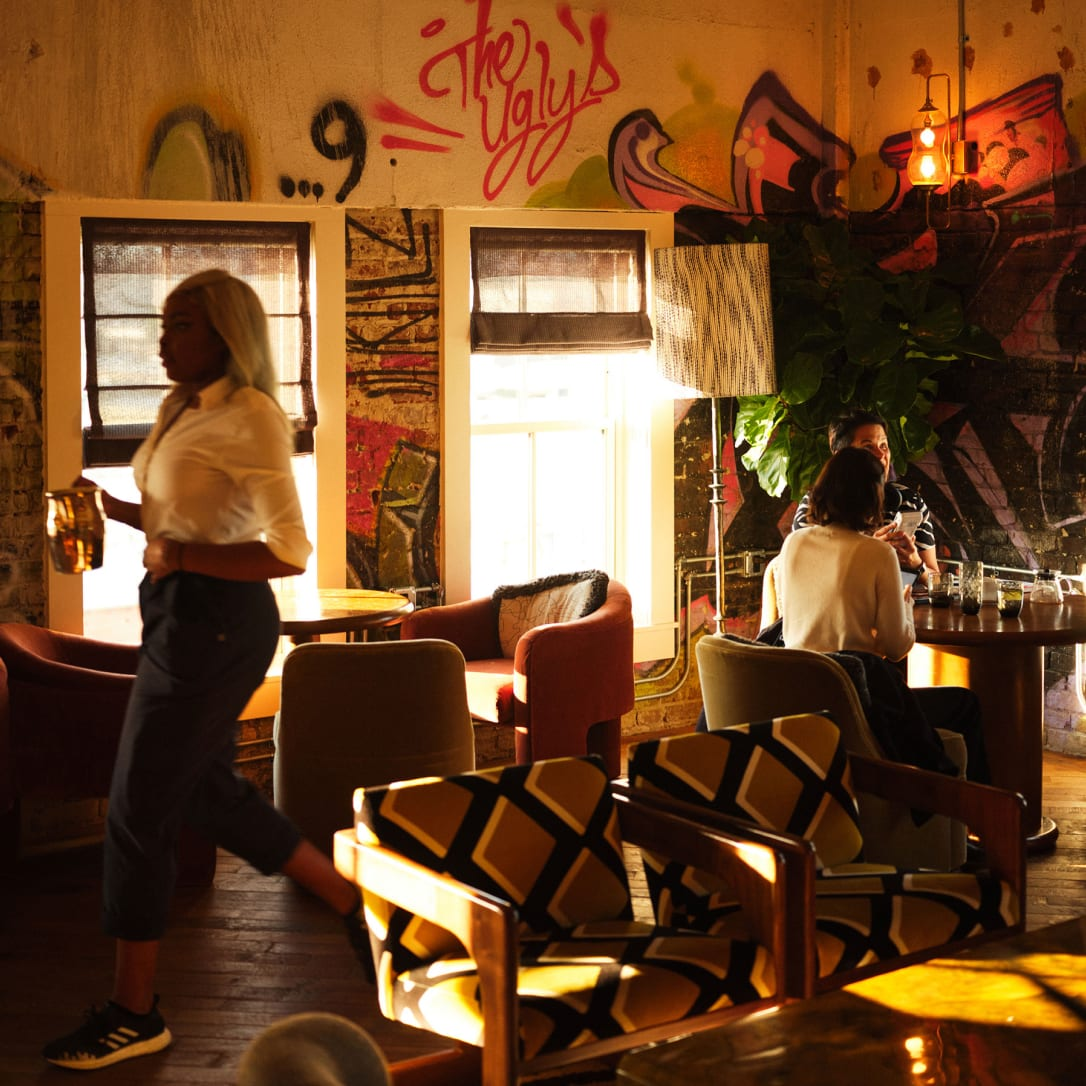 A waitress serving drinks in a lounge-like interior with graffiti on the walls.
