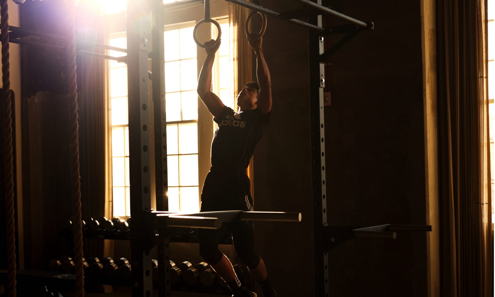 A man pulls himself up on rings in a gym.