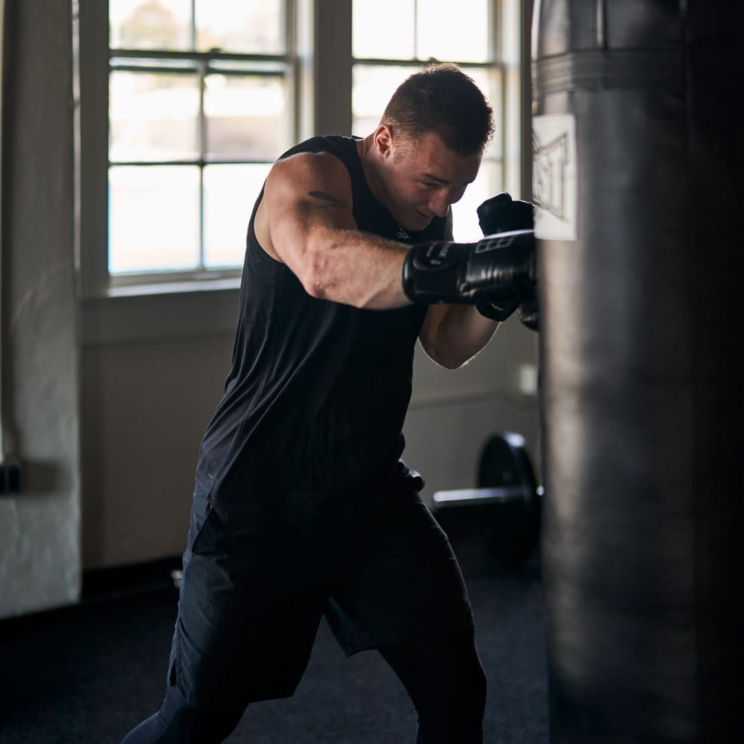 A man punches a punch bag in a gym.