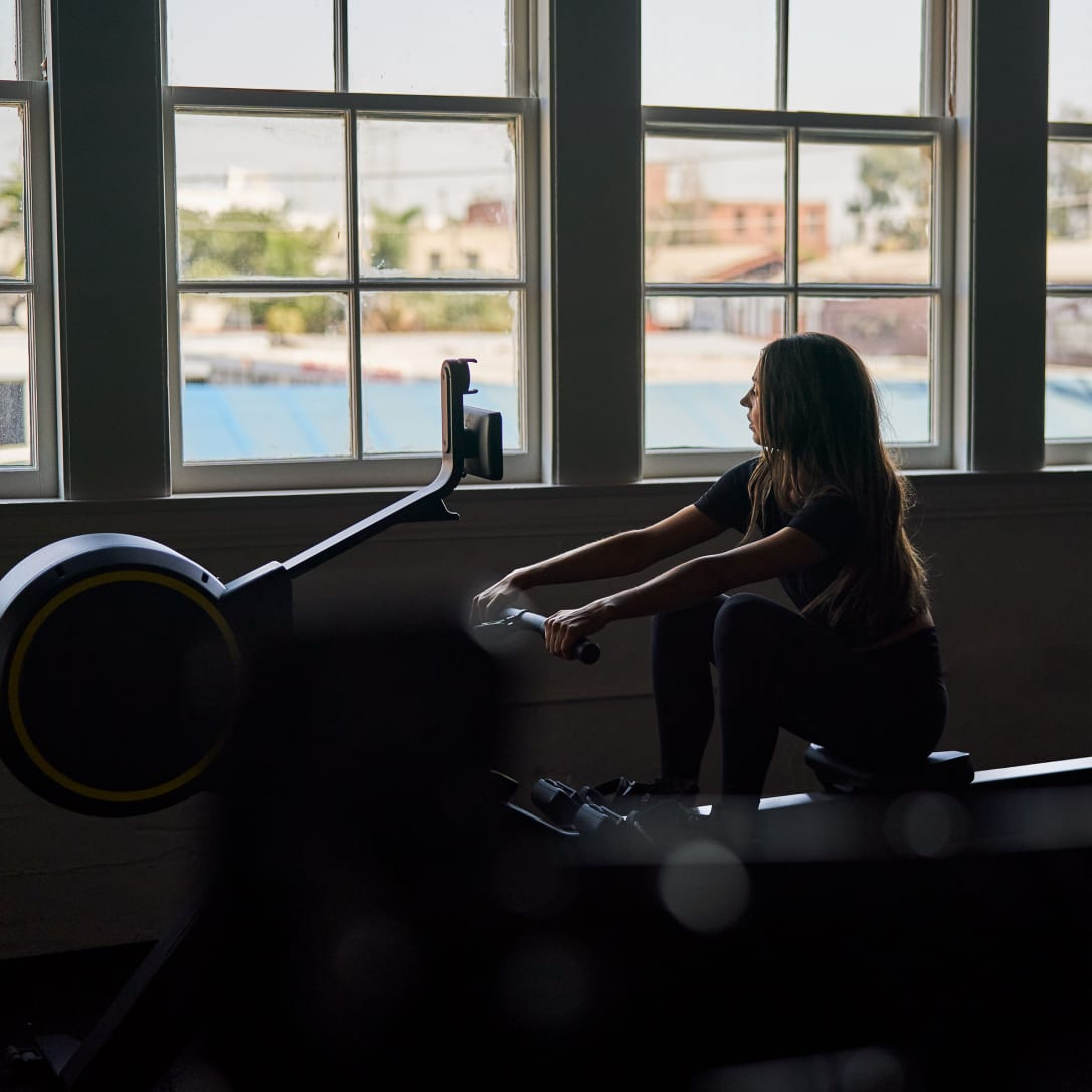A woman uses a rowing machine.