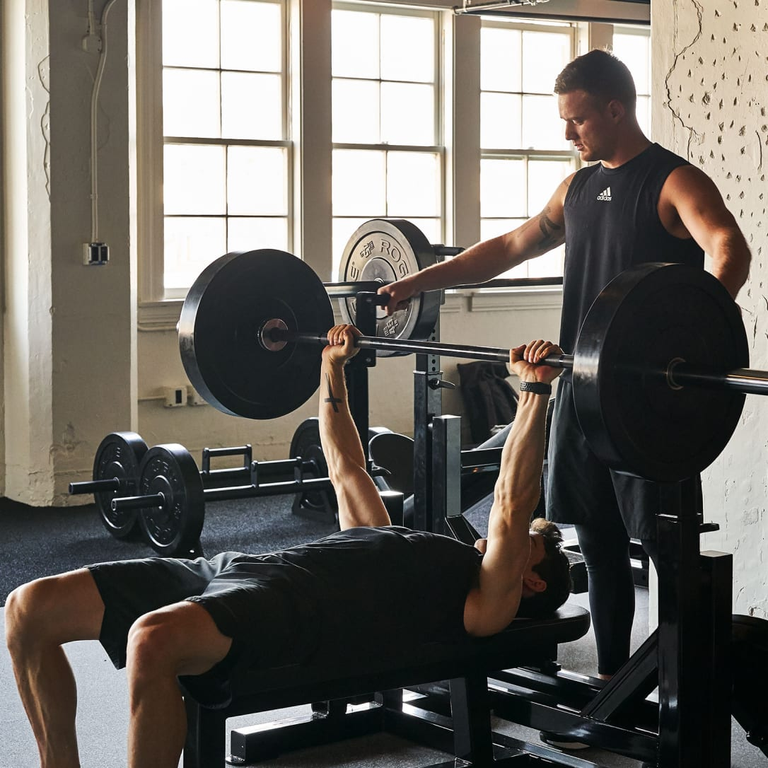 A man spots for another man lifting weights.
