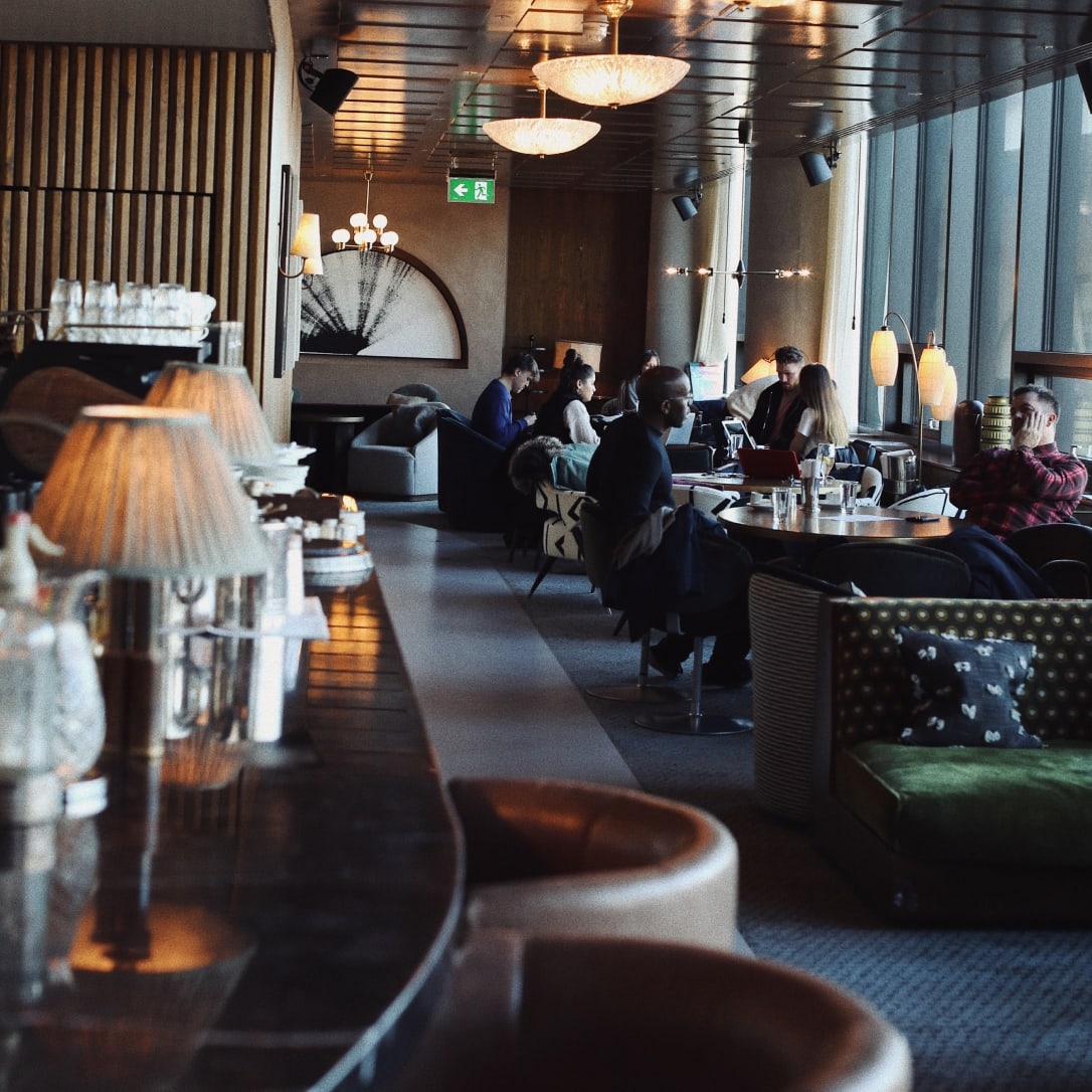 People sit and chat in the background of a bar and lounge-like interior.