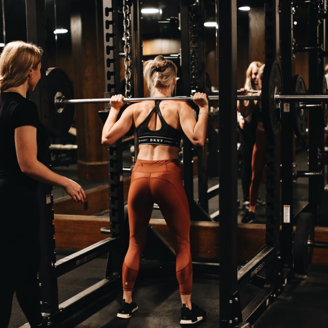 Two women working out using weights.