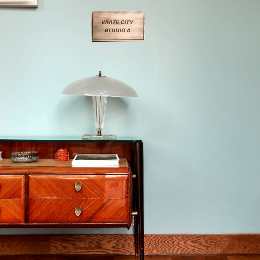 A side table with a lamp on it underneath a sign saying White City Studio A.