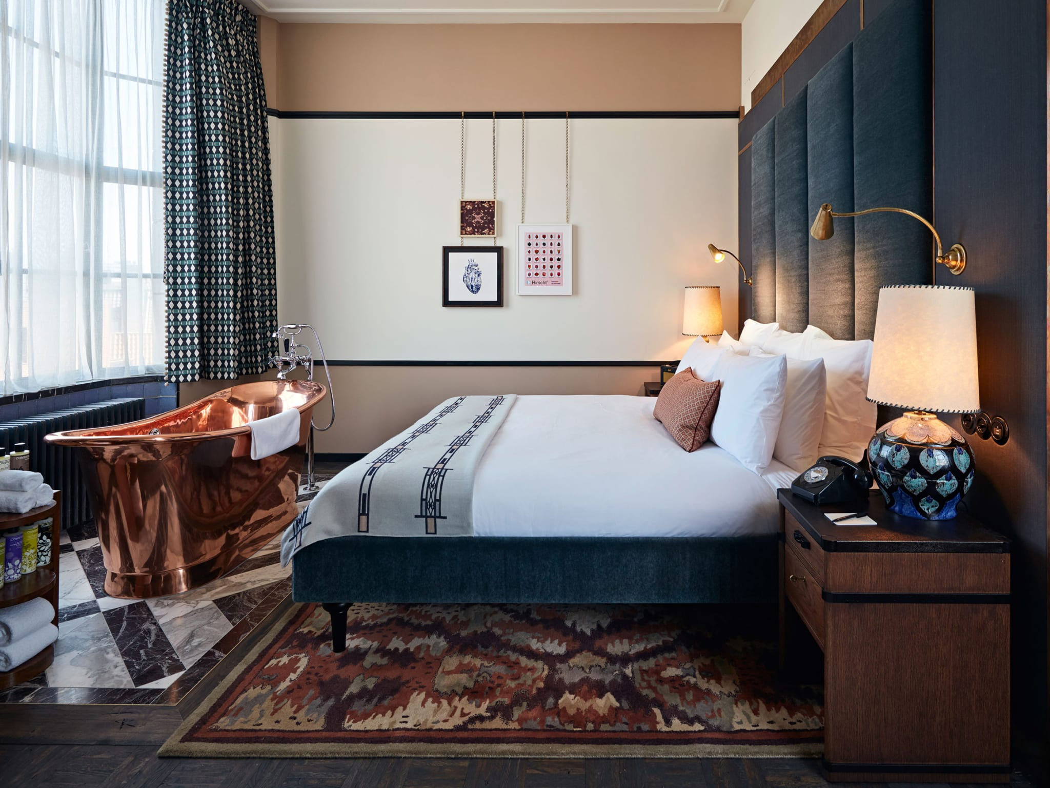 A bedroom with a copper bathtub at the end of the bed.